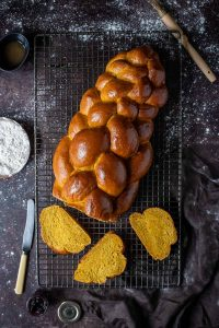 Vegan pumpkin challah bread on a wire rack on a dark background.