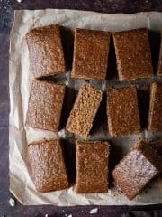 Vegan parkin cut into bars on a piece of brown baking parchment.