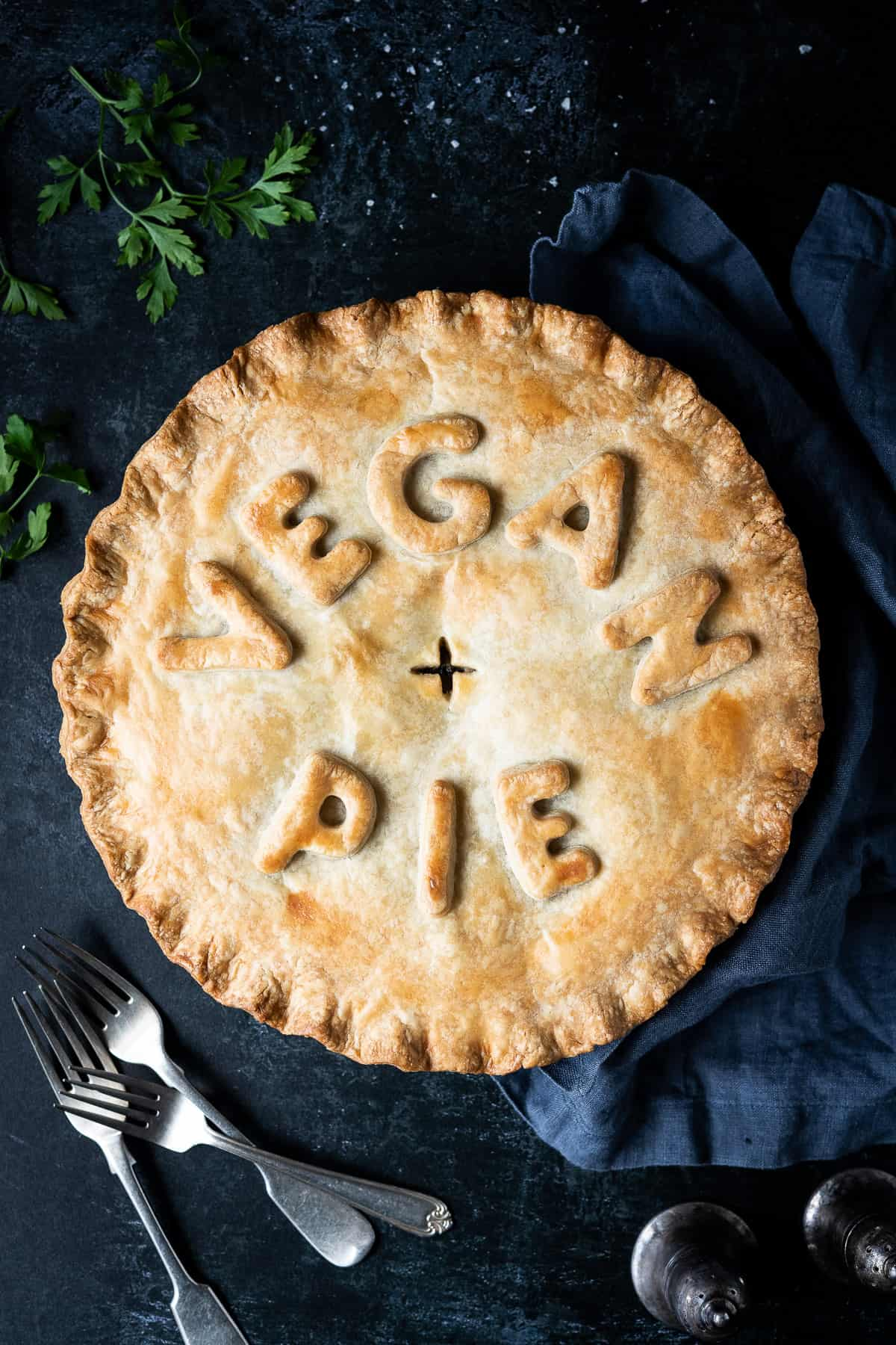 "Chickpea, leek and mushroom pie with the words ""vegan pie"" written on top, on a dark background with forks, parsley, salt and pepper shakers and a grey cloth."
