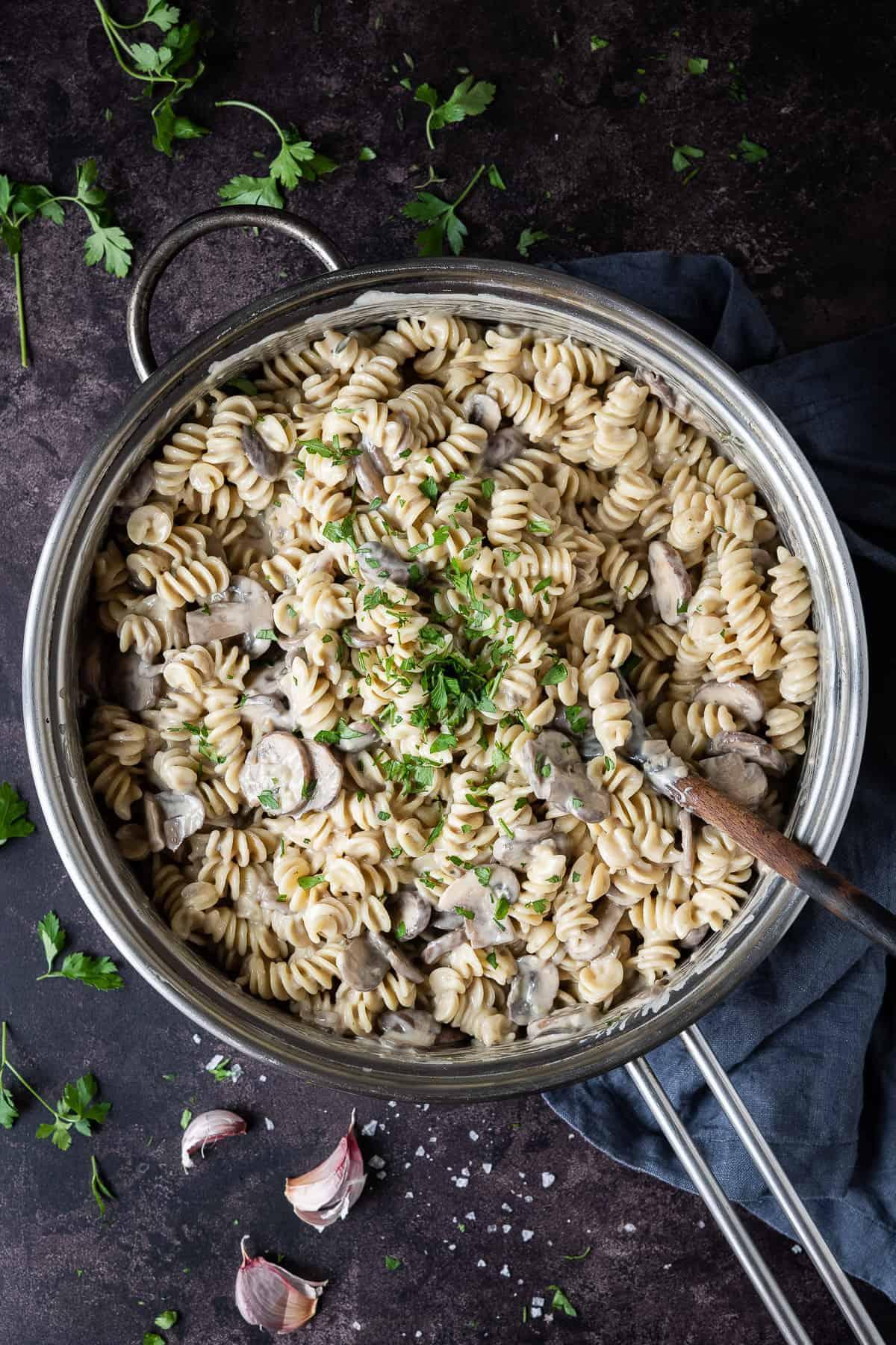 A metal pan of creamy vegan mushroom pasta on a dark surface with fresh parsley and garlic skins.