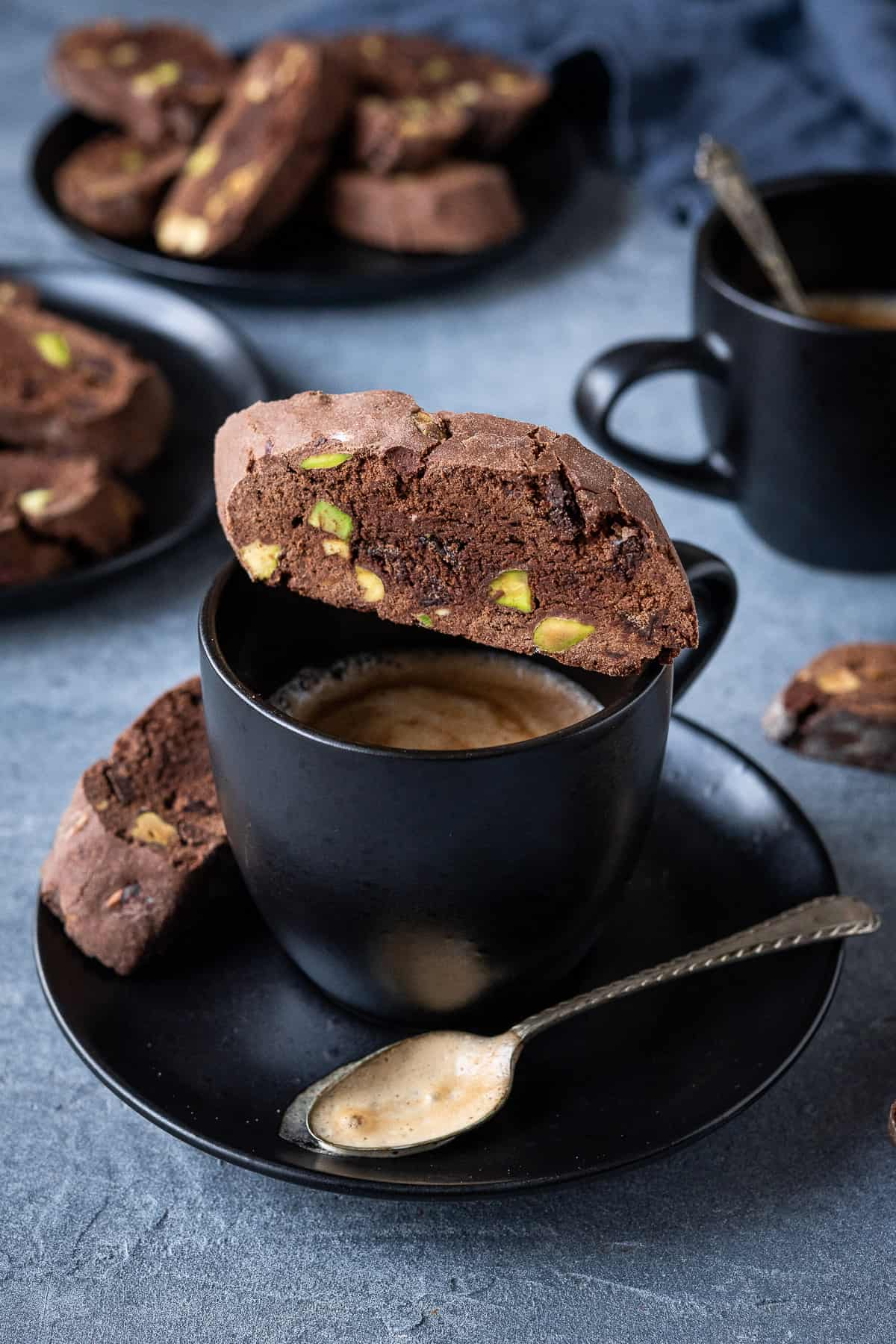 A vegan chocolate pistachio biscotti cookie balanced on top of a black coffee cup.