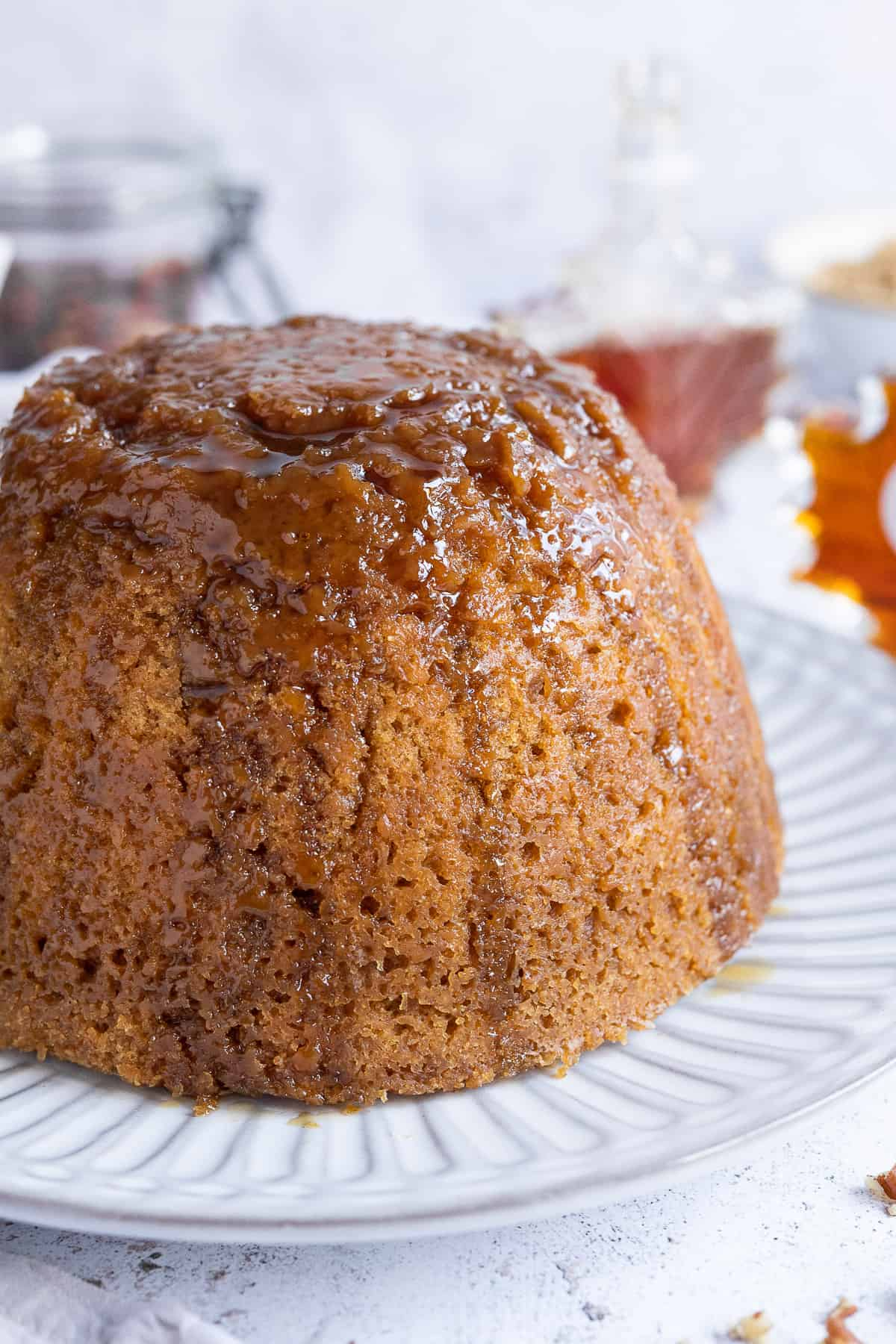 Close up of vegan steamed maple syrup pudding topped with a drizzle of maple syrup.