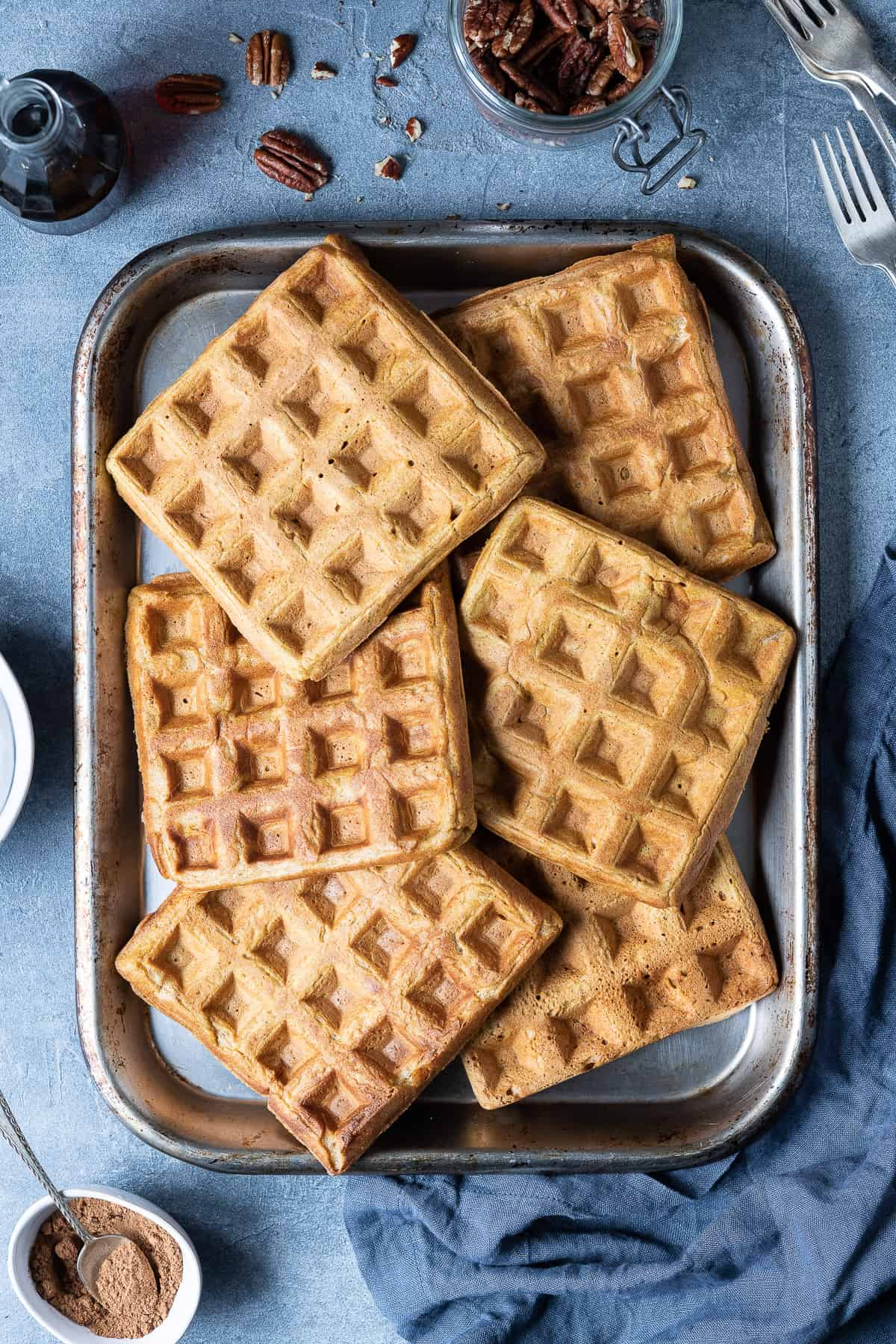 Pumpkin waffles on a metal baking tray on a grey background.