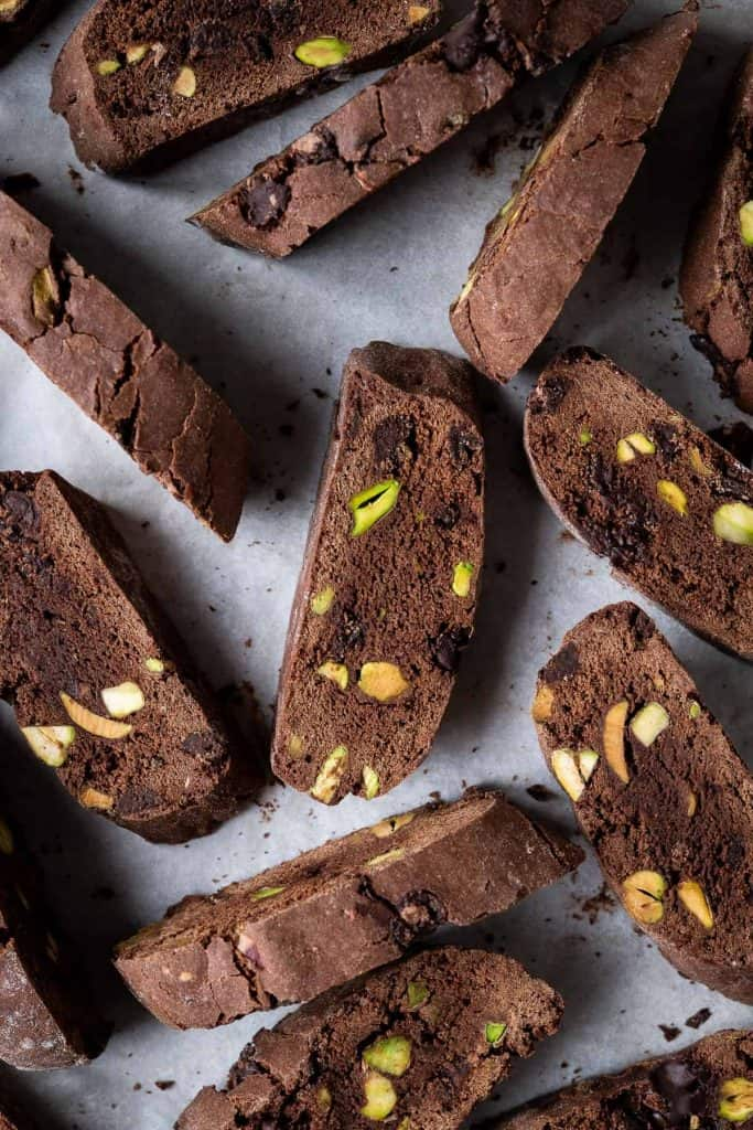 Vegan chocolate pistachio biscotti on a sheet of white baking parchment.