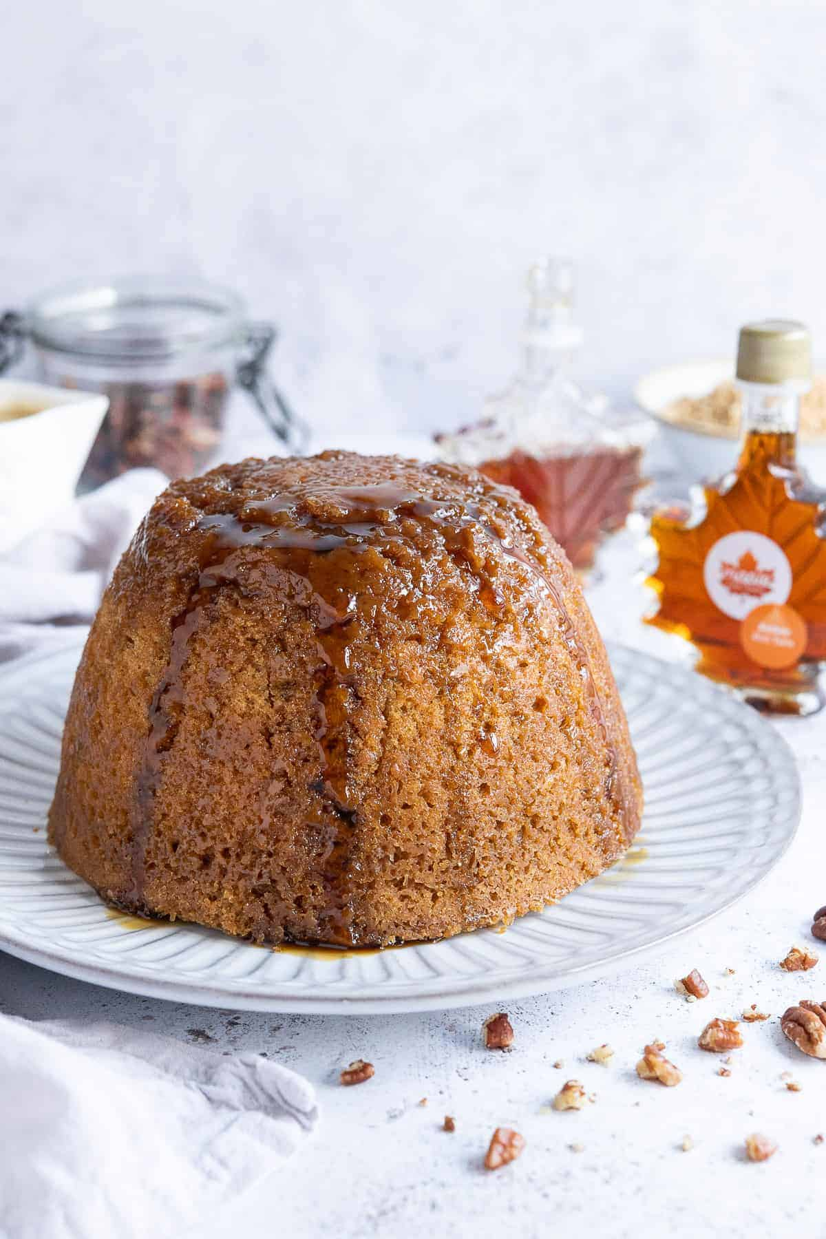 Vegan steamed maple syrup pudding on a white plate with bottles of maple syrup, a jug of custard and a jar on pecans in the background.