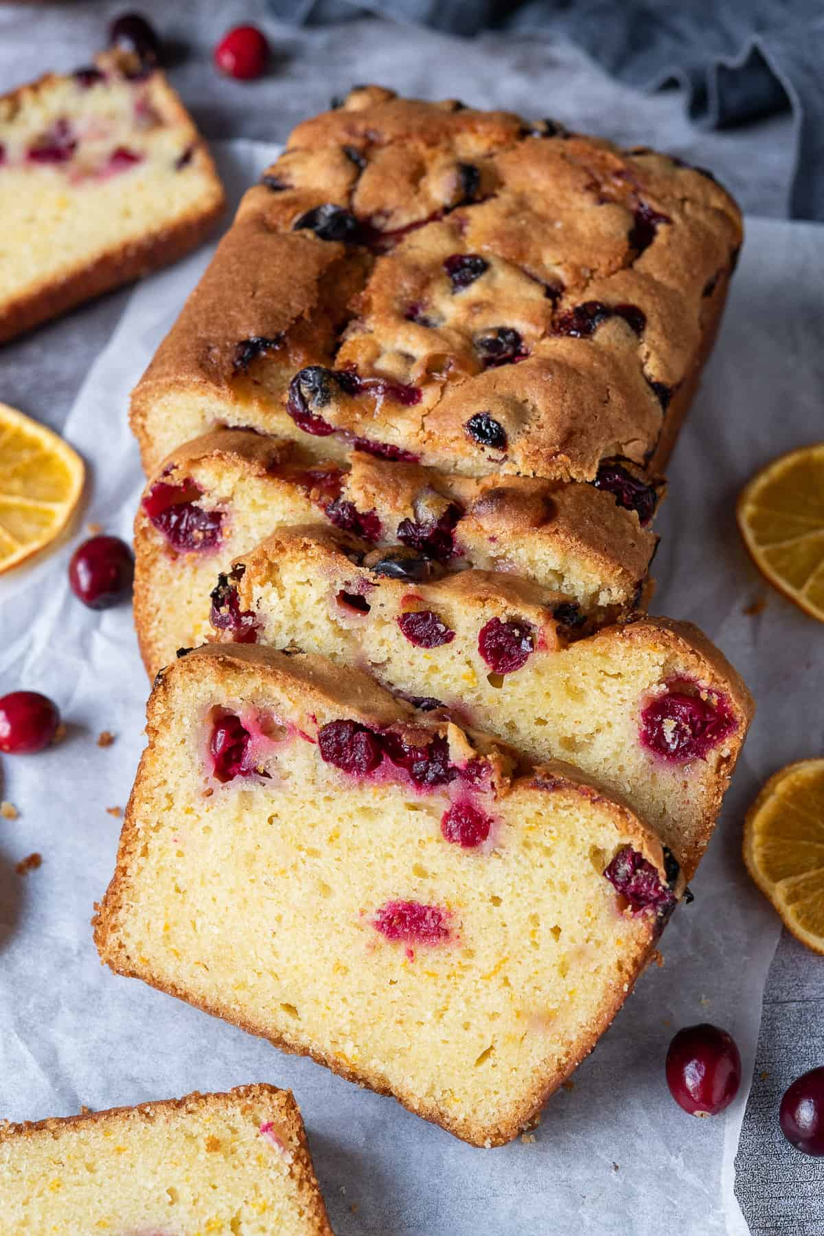 Sliced cranberry orange bread on a sheet of baking parchment on a grey background.