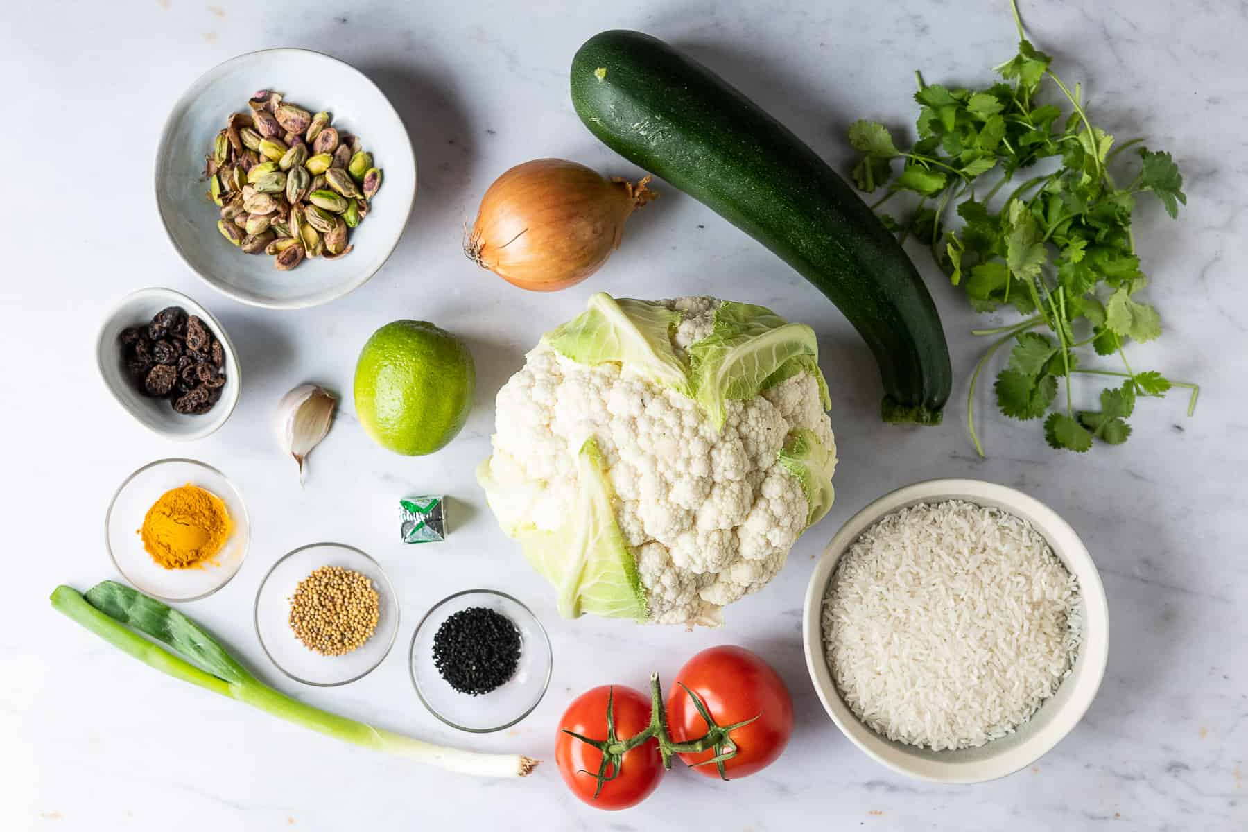 A shot of the ingredients needed to make spiced cauliflower and courgette with yellow rice.
