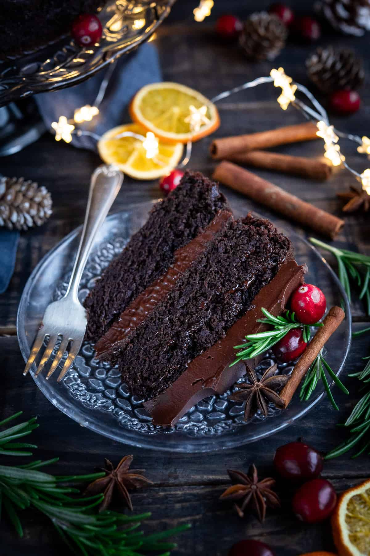 A slice of chocolate cake on a glass plate with a fork, surrounded by festive decorations.