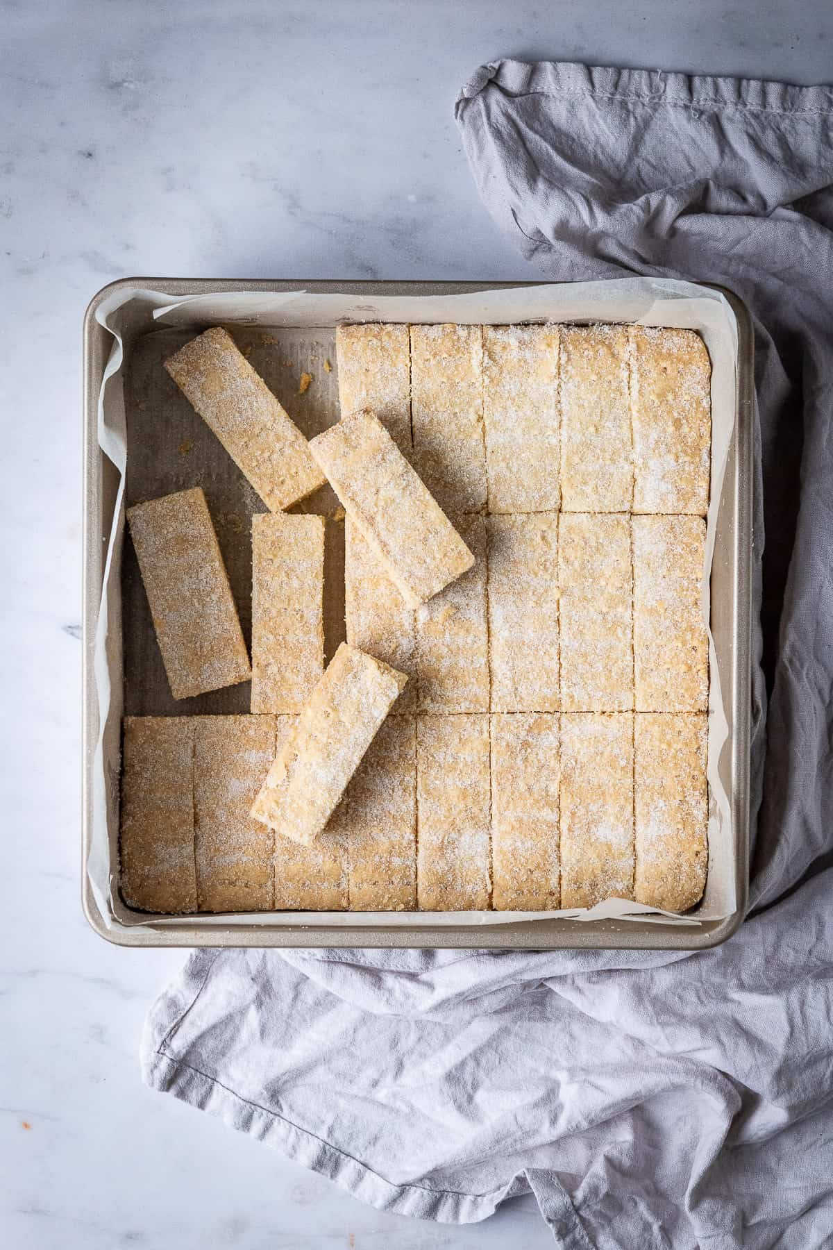 Vegan shortbread fingers in a square metal cake tin on a marble background with a grey cloth.