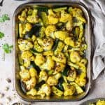 A roasting tray of spiced cauliflower and courgette with a bowl of yellow rice, a bowl of tomato salsa, a cloth, half a lime, pistachios and fresh coriander leaves.