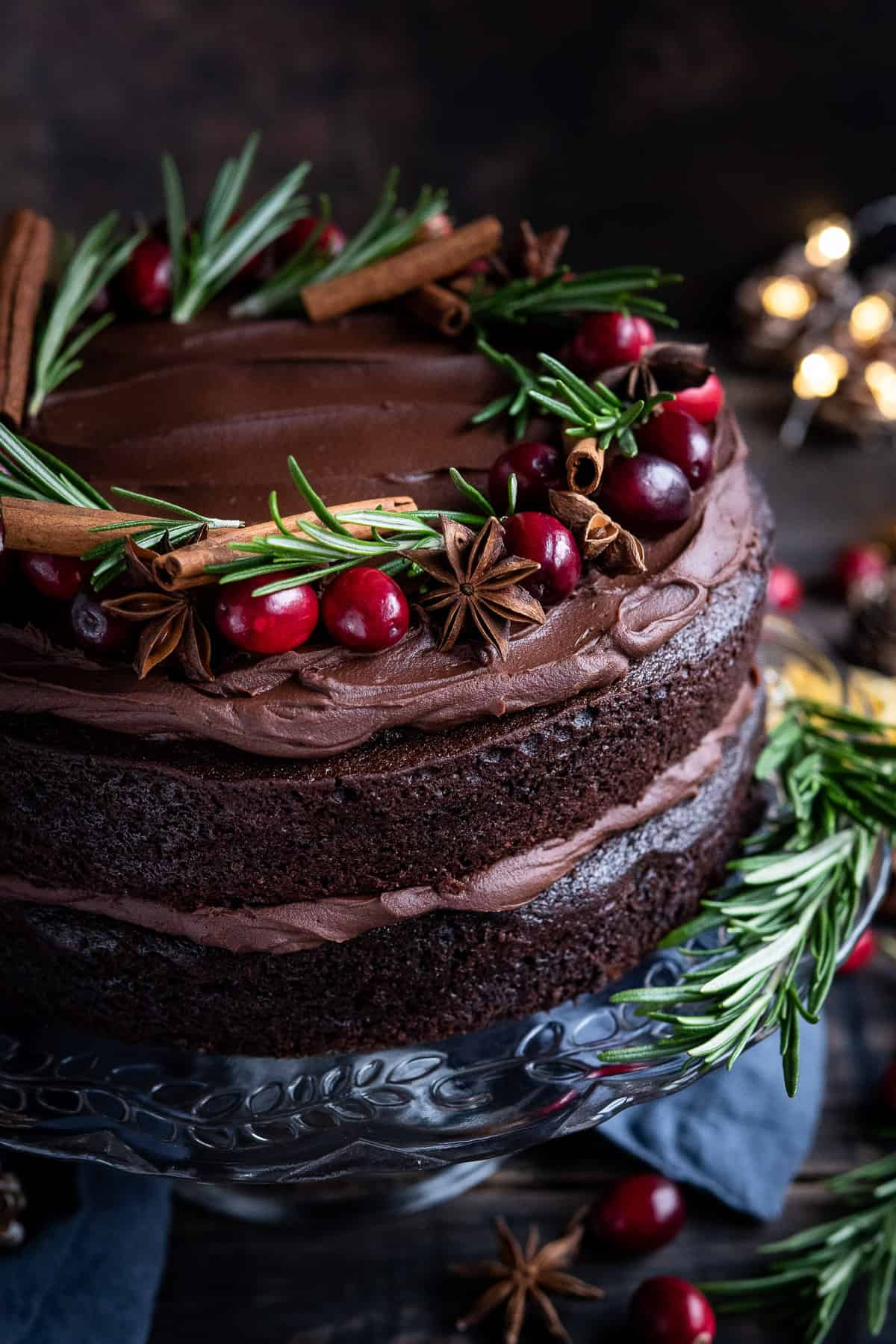 Close up of vegan mulled wine chocolate cake topped with fresh cranberries, rosemary, star anise and cinnamon sticks.