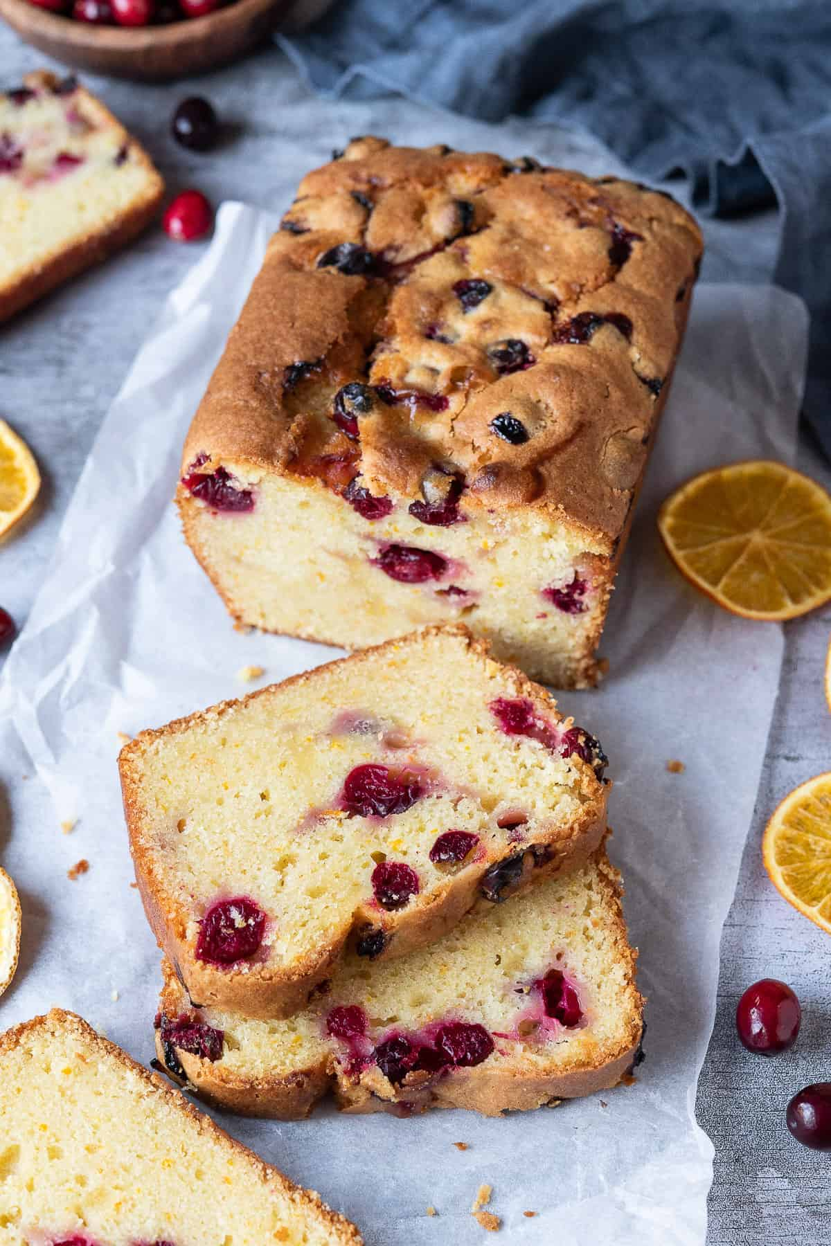 Vegan orange cranberry cake on a sheet of white baking parchment with dried orange slices and fresh cranberries.