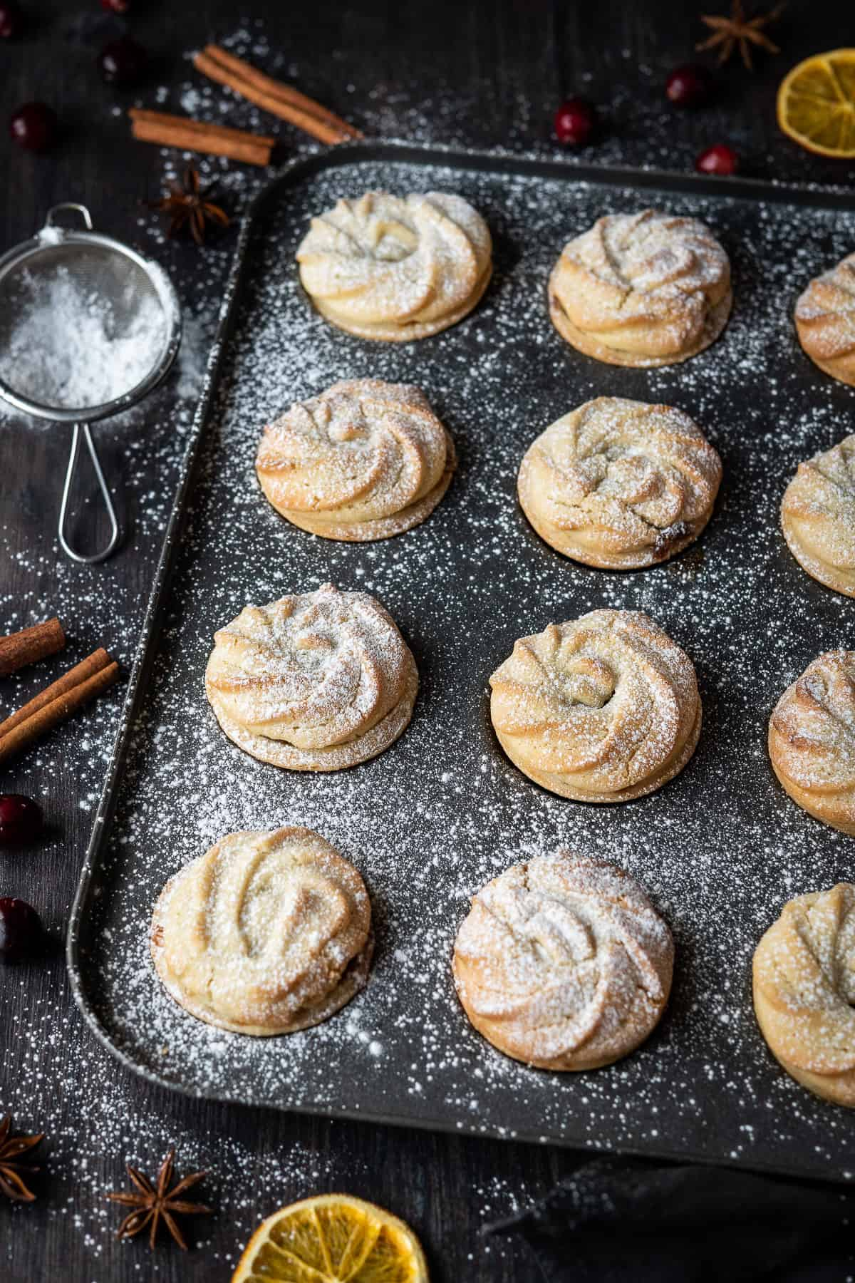 Vegan viennese whirl mince pies in a metal bun tin on a wooden table with a mini sieve full of icing sugar, whole spices and dried orange slices.