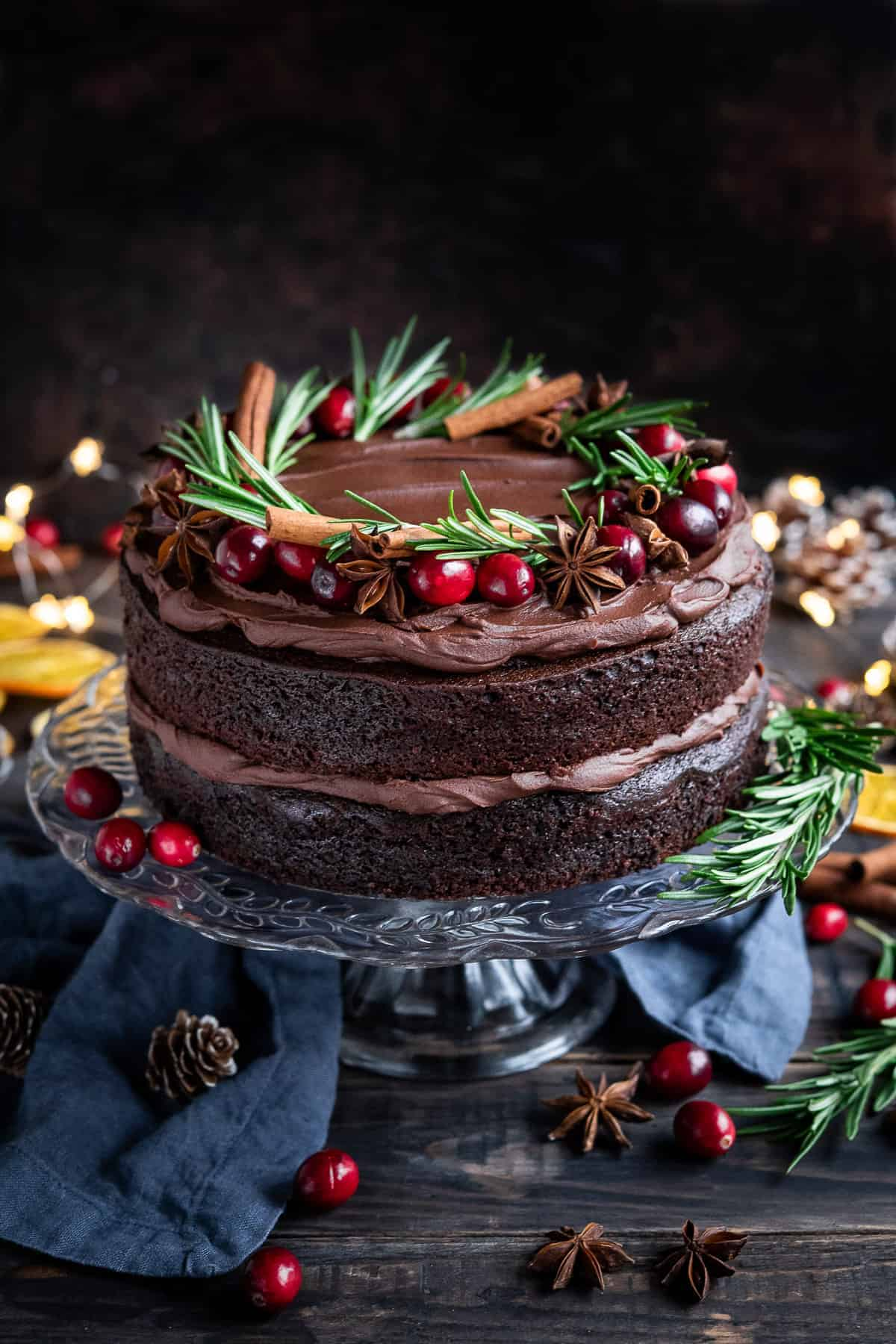 Vegan mulled wine chocolate cake topped with cranberries, rosemary, star anise and cinnamon sticks on a glass cake stand on a wooden table.