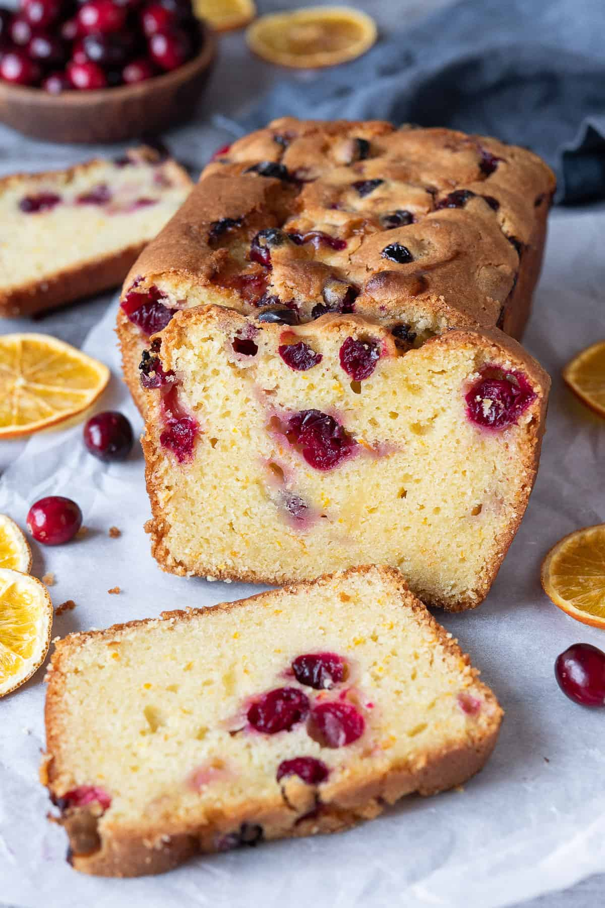 Vegan orange cranberry cake with three slices cut with dried orange slices and a bowl of fresh cranberries in the background.