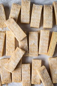 Vegan shortbread fingers in rows on a sheet of white baking parchment.