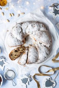 Vegan stollen wreath on a sheet of white baking parchment on a blue surface with christmas decorations and lights.
