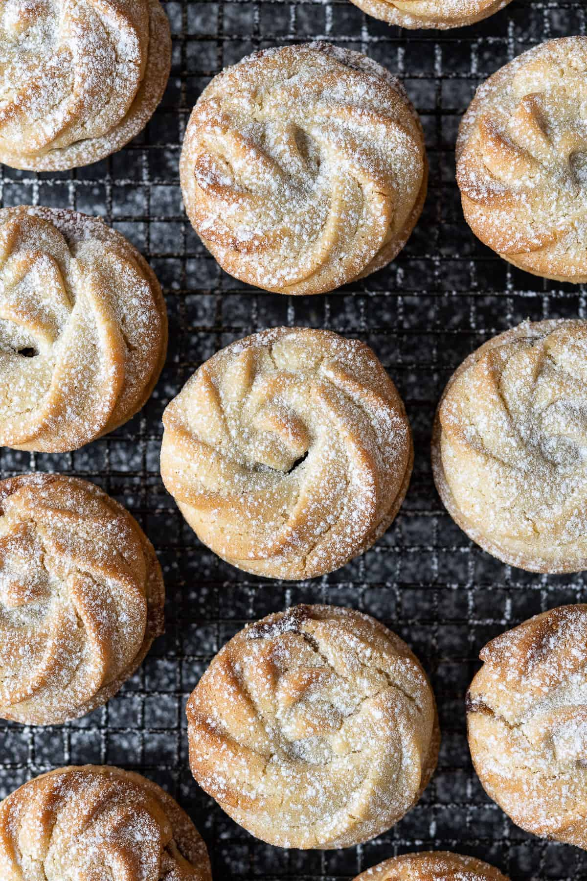 Top down shot of vegan viennese whirl mince pies on a metal cooling rack.