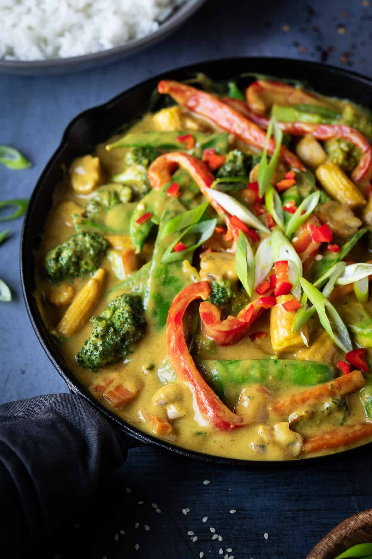 Close up of Chinese vegetable curry in a black skillet.