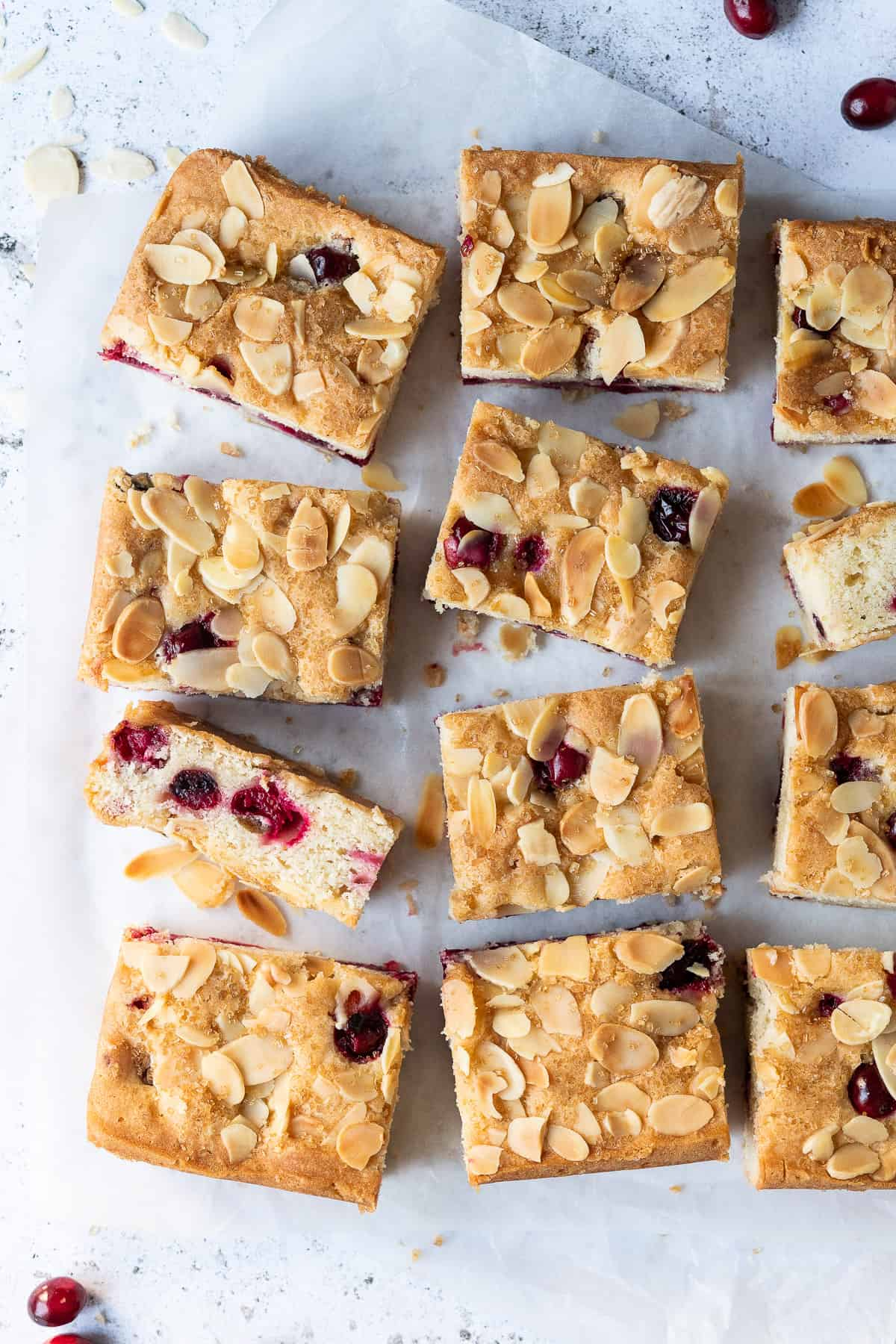 Squares of cranberry almond cake on a sheet of white baking parchment.