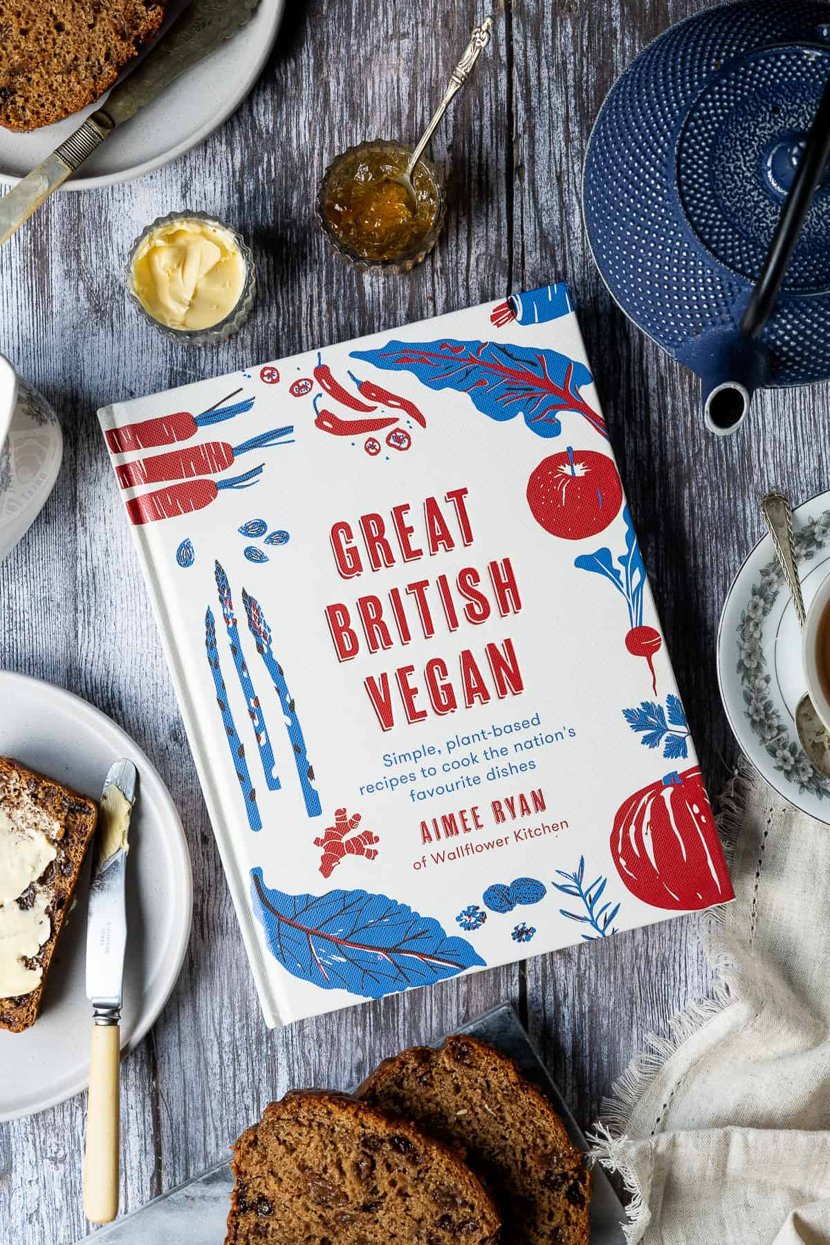 Great British Vegan cookbook on a wooden table surrounded by breakfast crockery.