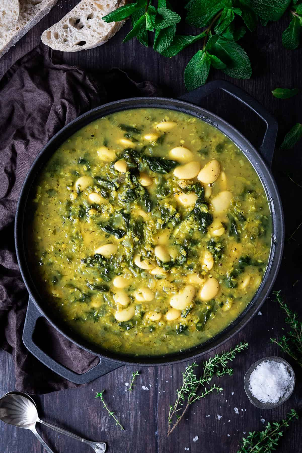 Spinach, lentil and butter bean soup in a black pan on a wooden table with fresh herbs, slices of bread and a bowl of salt.