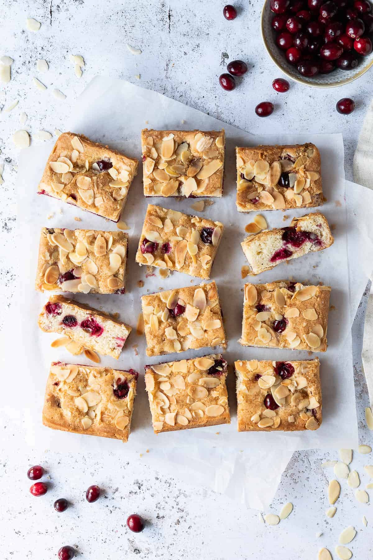 Vegan almond cranberry cake sliced into bars on a sheet of baking parchment on a white background with a bowl of fresh cranberries.