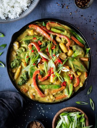 Vegan Chinese curry with vegetables in a black skillet on a metal surface with a bowl of rice, chilli flakes and sliced spring onions.