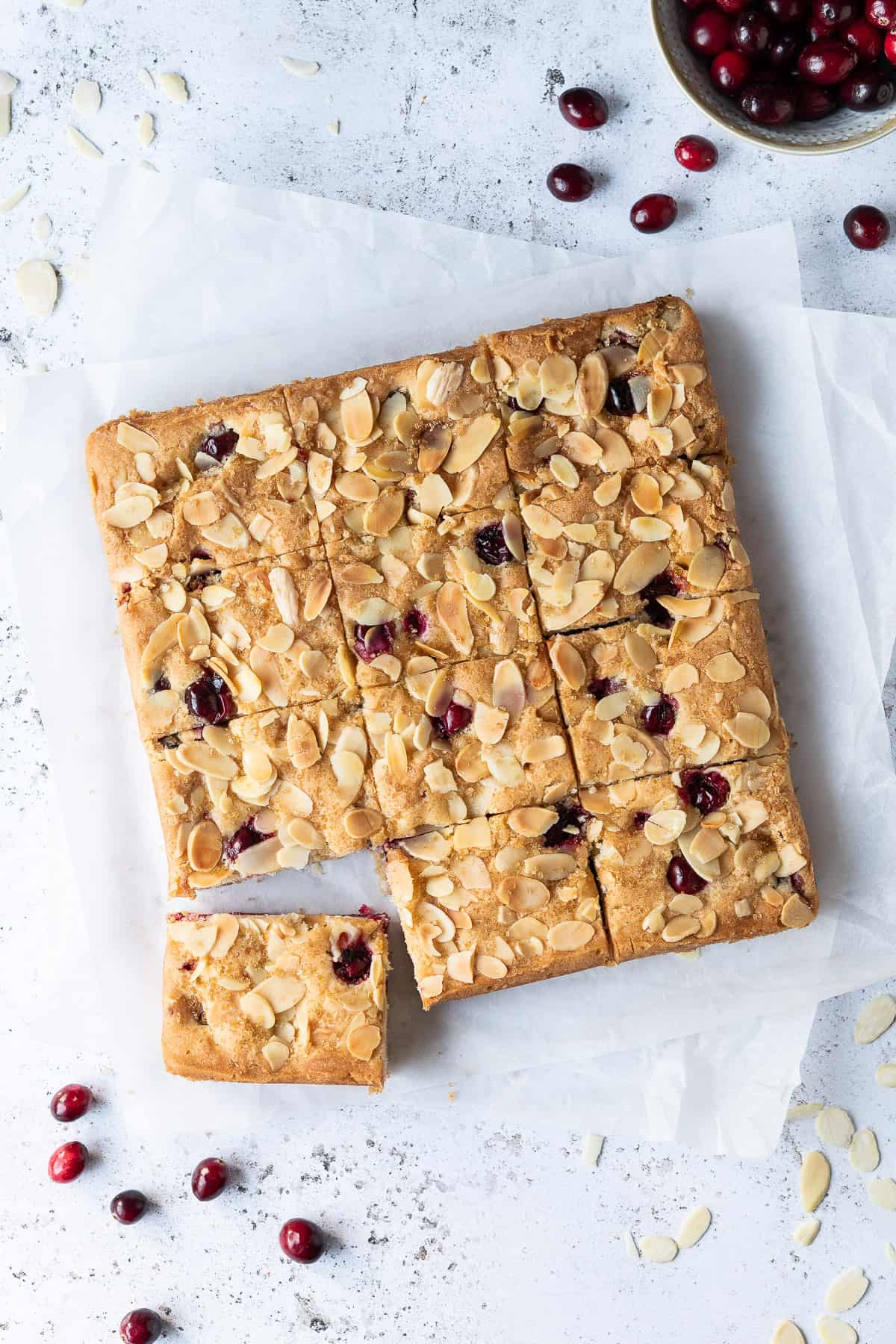 Vegan cranberry almond cake on a sheet of white baking parchment on a white surface with fresh cranberries.