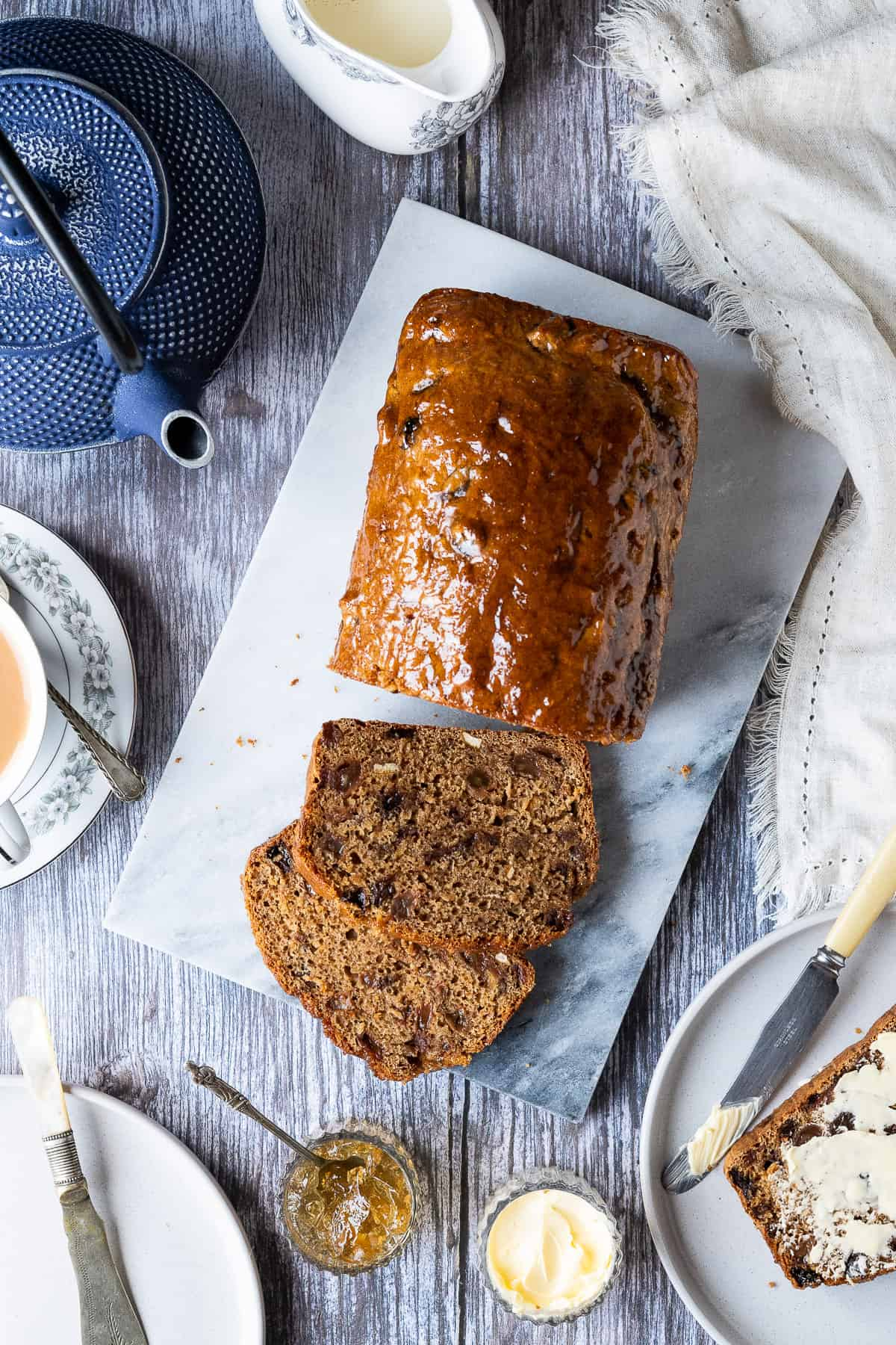 Vegan Earl Grey tea loaf on a marble board on a wooden table with a blue teapot, plates, knives, bowls of butter and marmalade, cup of tea and jug of milk.
