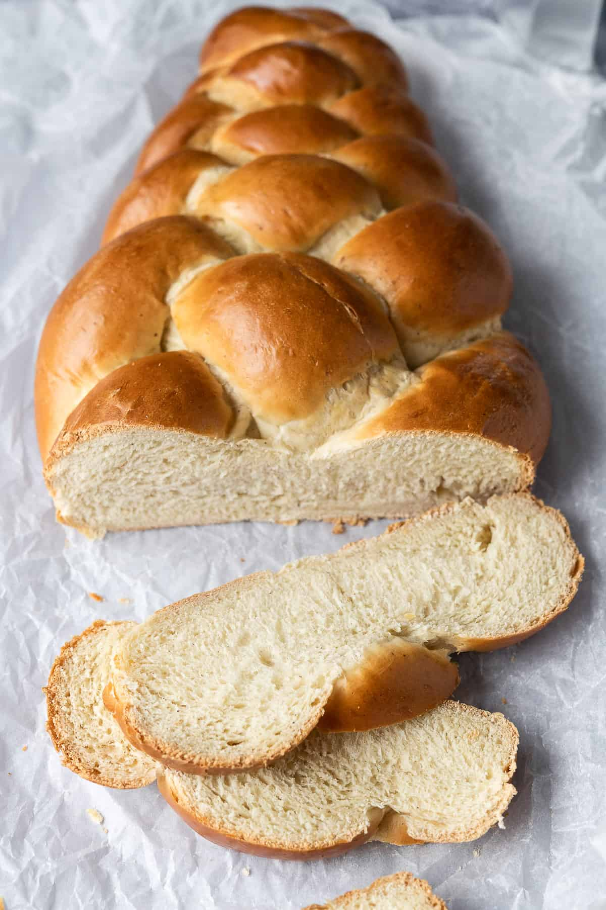 The sliced loaf of pulla bread on white baking parchment.