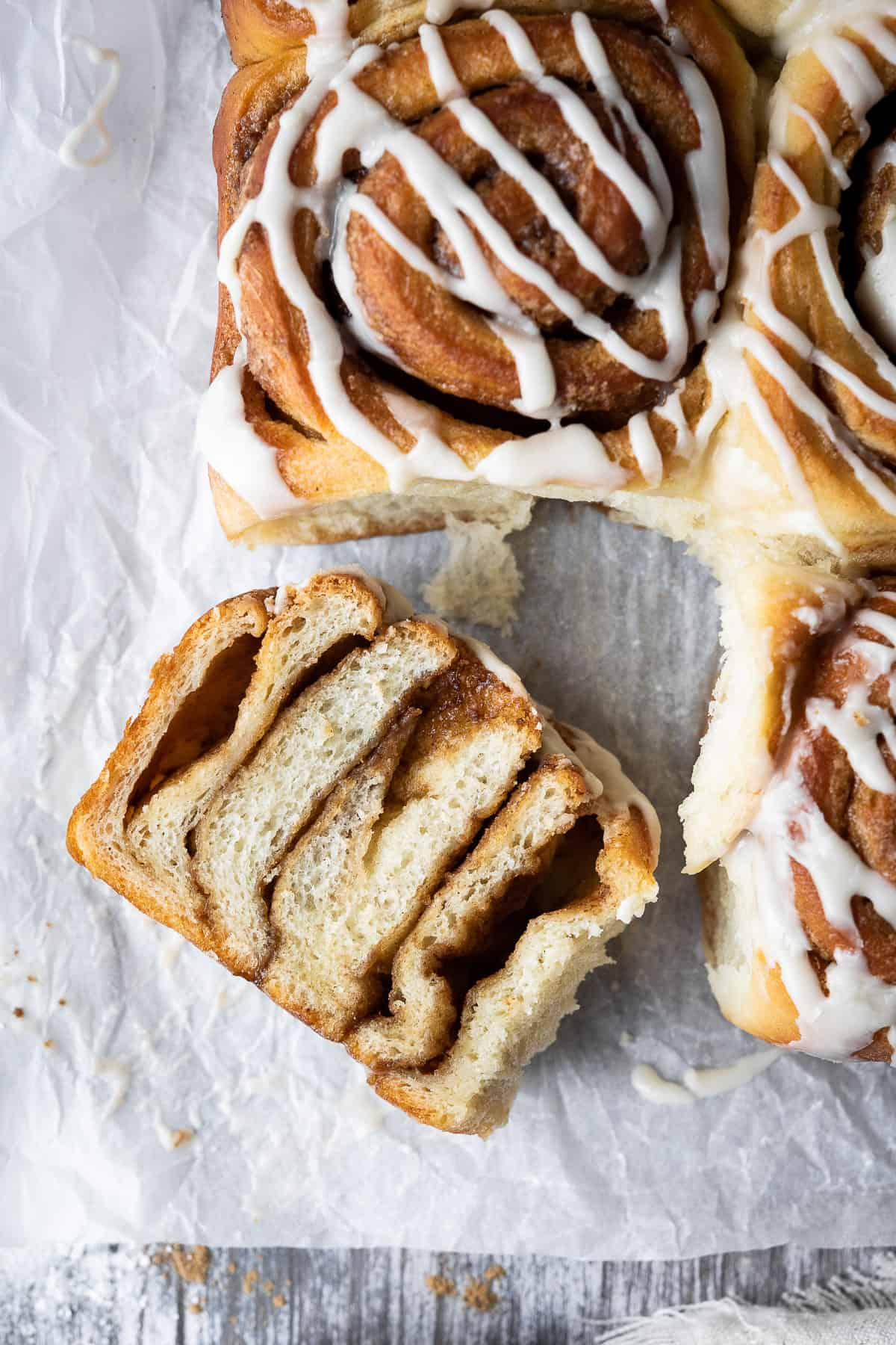 A cinnamon roll sliced in half on white baking parchment.