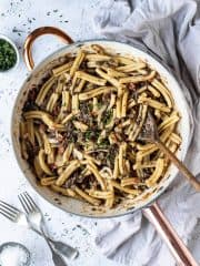A white pan full of sun dried tomato puy lentil pasta on a white surface with a grey cloth, two forks, bowl of salt and bowl of thyme leaves.