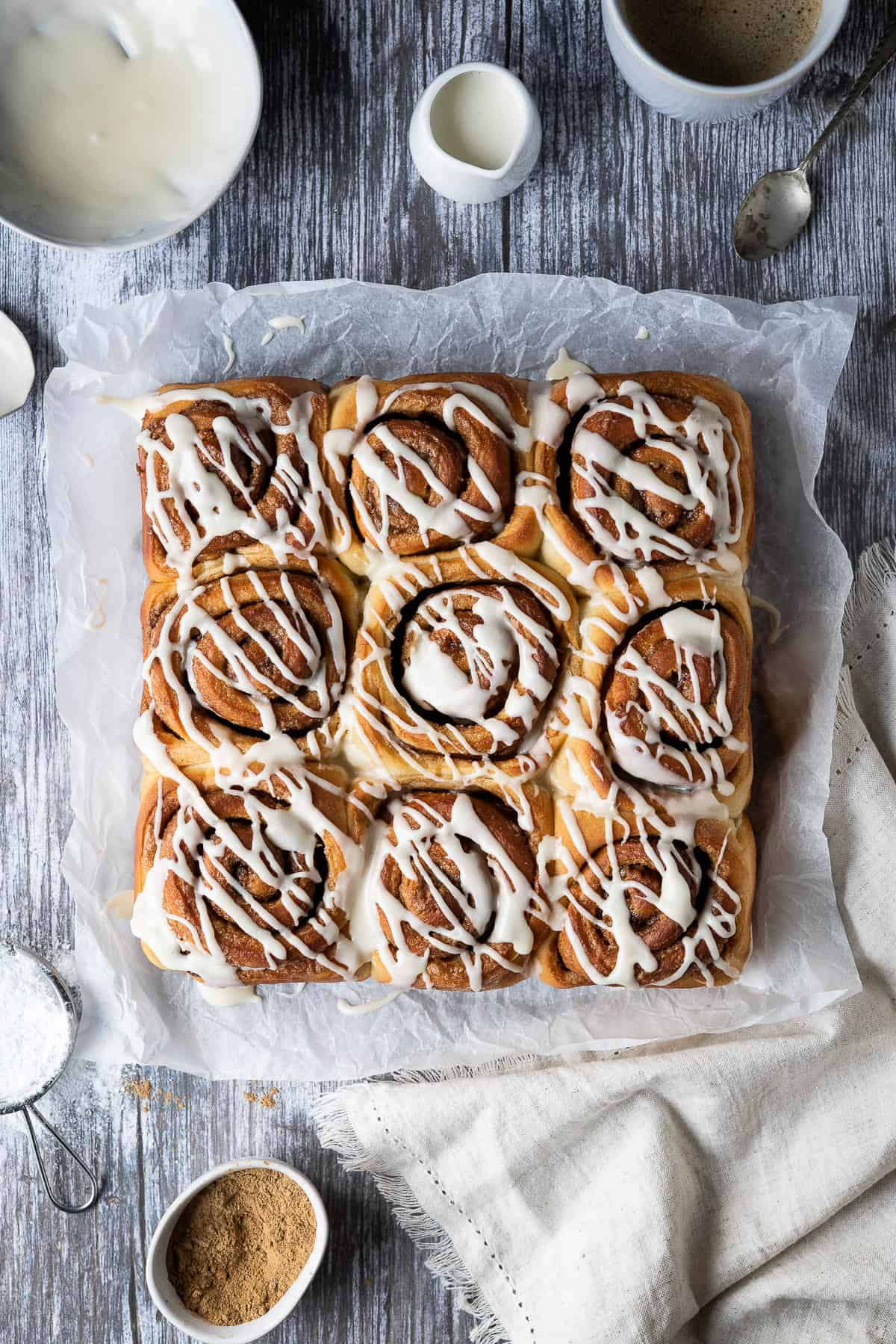 Vegan cinnamon rolls on a sheet of baking parchment on a wooden table surrounded by a bowl of glaze, jug of milk, cup of coffee, beige cloth and bowl of cinnamon.