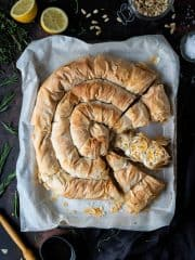 Vegan butternut squash and feta filo pie with three slices cut out on a baking parchment lined baking tray on a dark table surrounded by herbs, a halved lemon, jar of pine nuts, bowl of olive oil and a pastry brush.