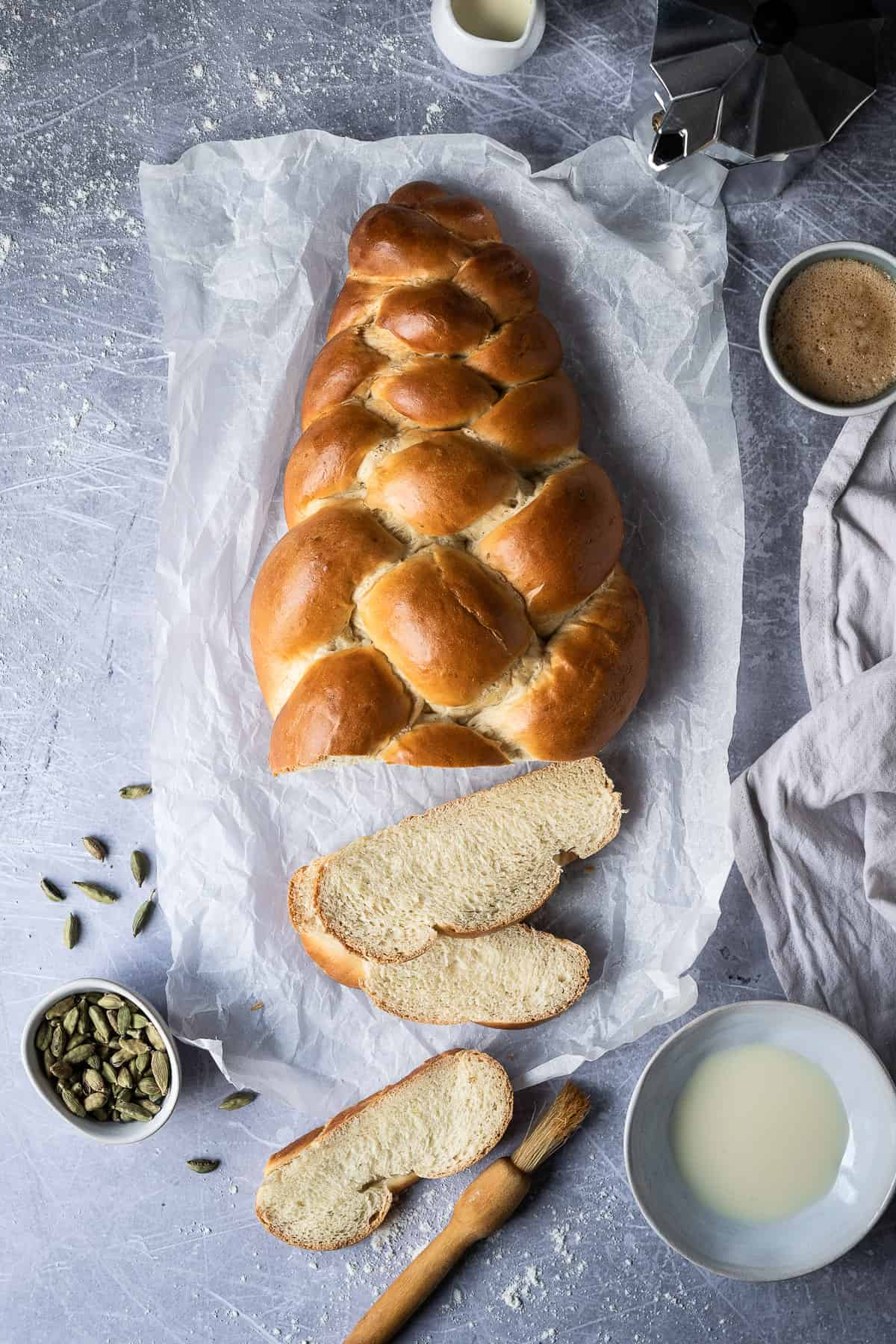 Vegan pulla bread with three pieces sliced off on a sheet of baking parchment on a metal surface with a bowl of cardamom pods, bowl of milk and pastry brush, cup of coffee and a caffetiere.