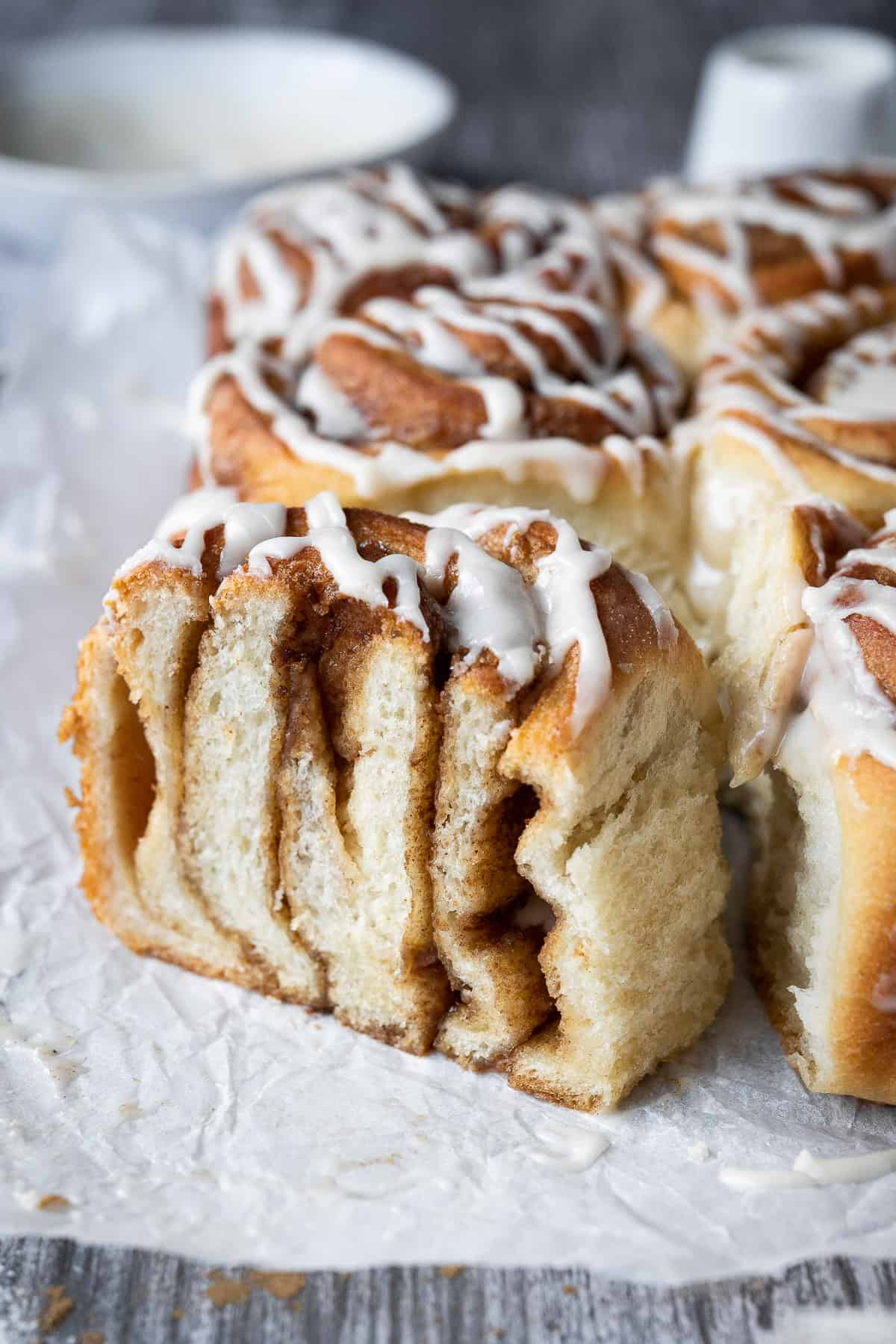 Close up of a cinnamon roll which has been sliced in half.
