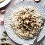 Vegan mushroom risotto topped with fried shiitake mushrooms on a white plate with a bowl of rocket, some fresh mushrooms and thyme.
