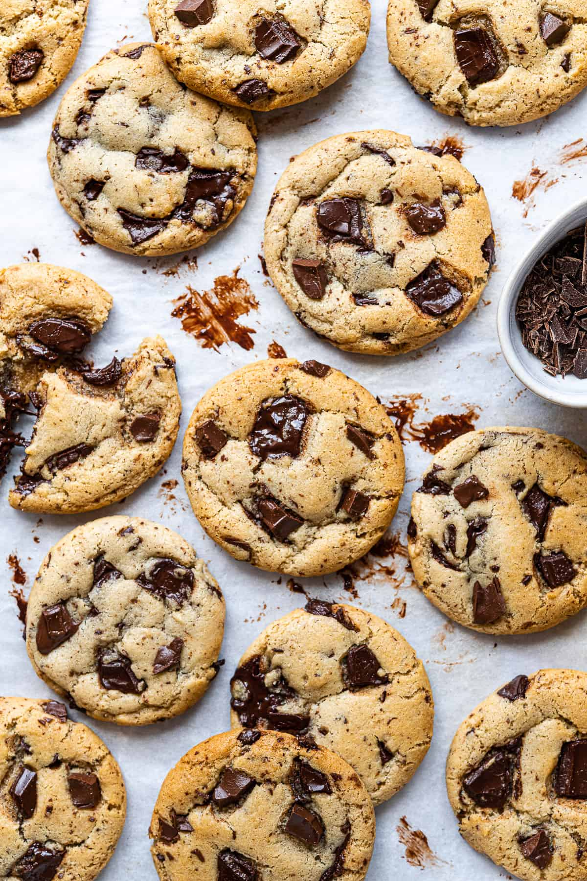 Olive oil chocolate chip cookies on a sheet of white baking parchment.