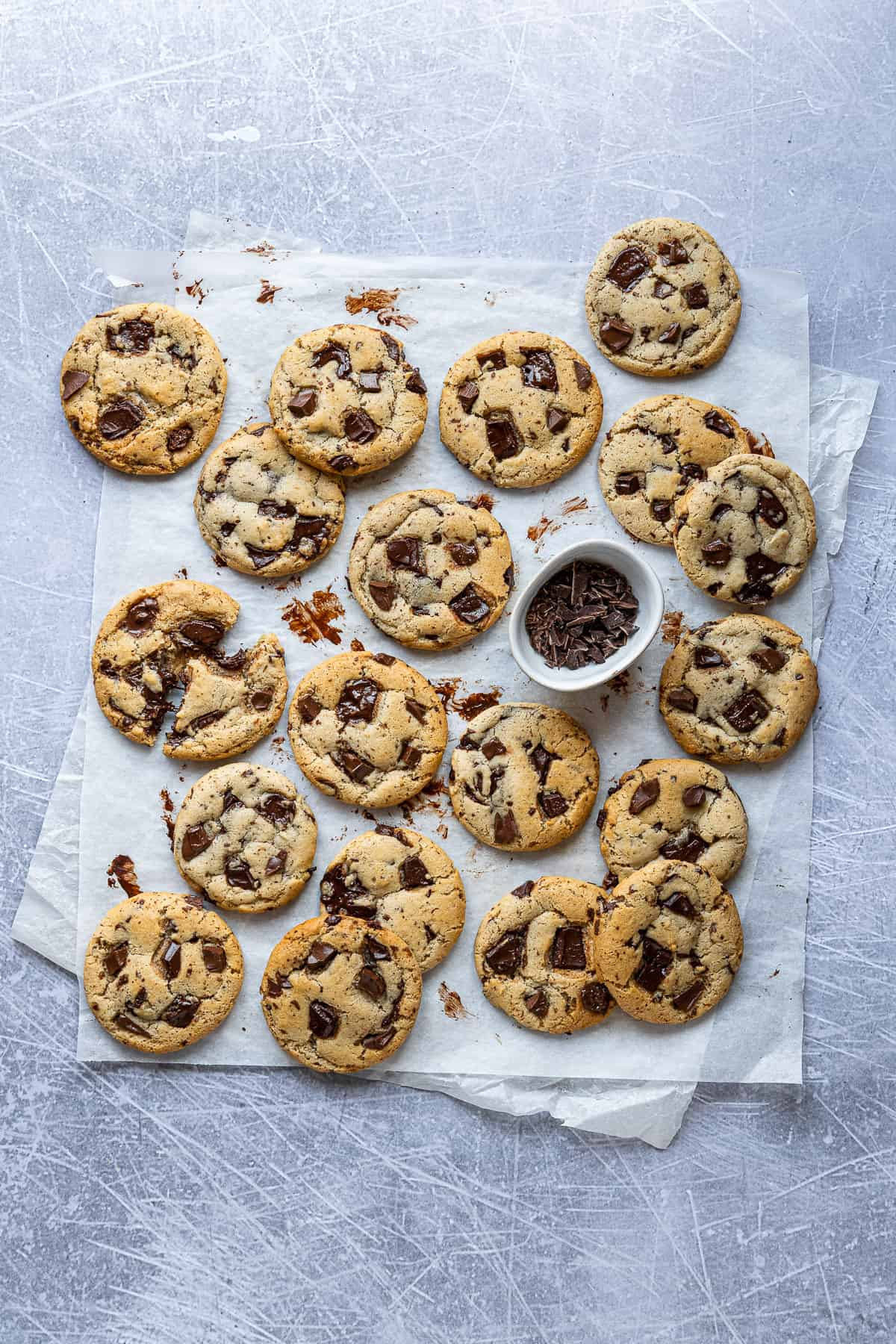 Chocolate chip cookies and a bowl of chopped chocolate on a sheet of white baking parchment on a metal surface.