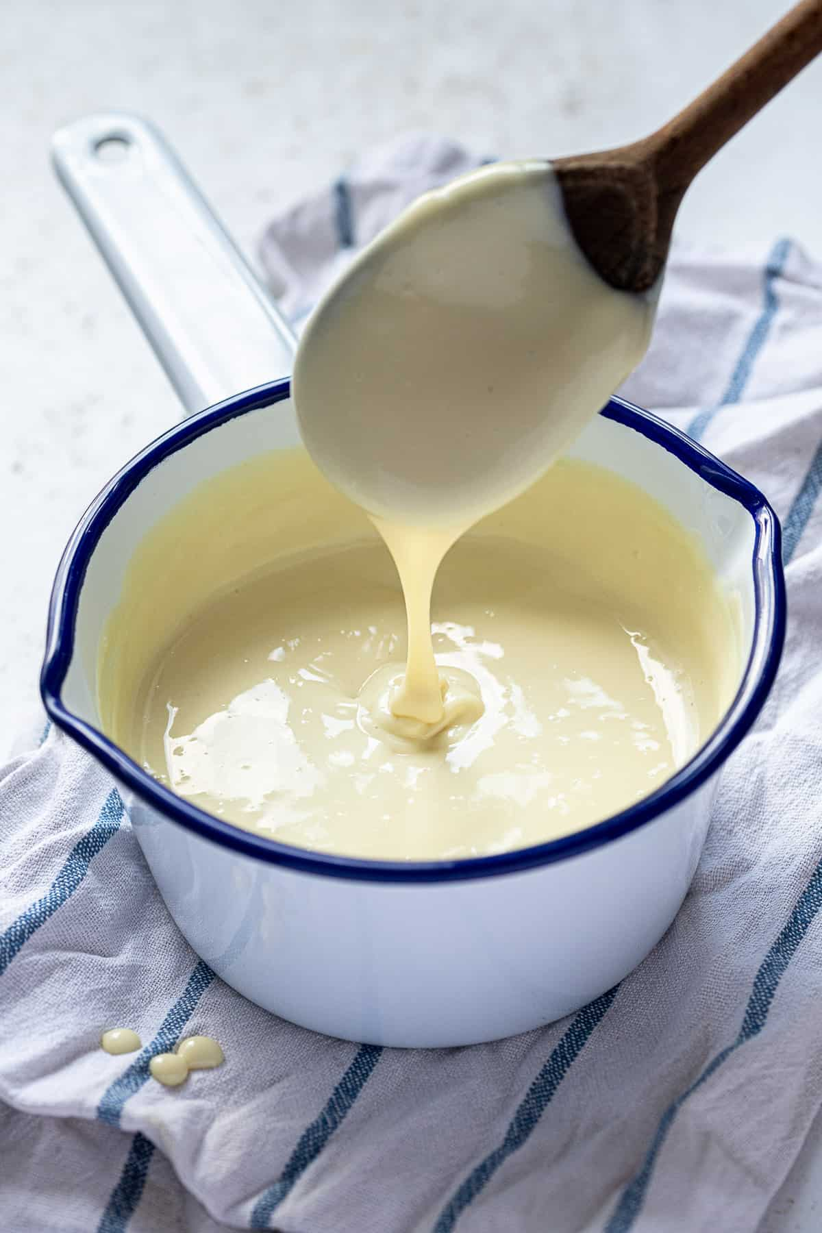 Vegan custard being drizzled off a wooden spoon into a pan.