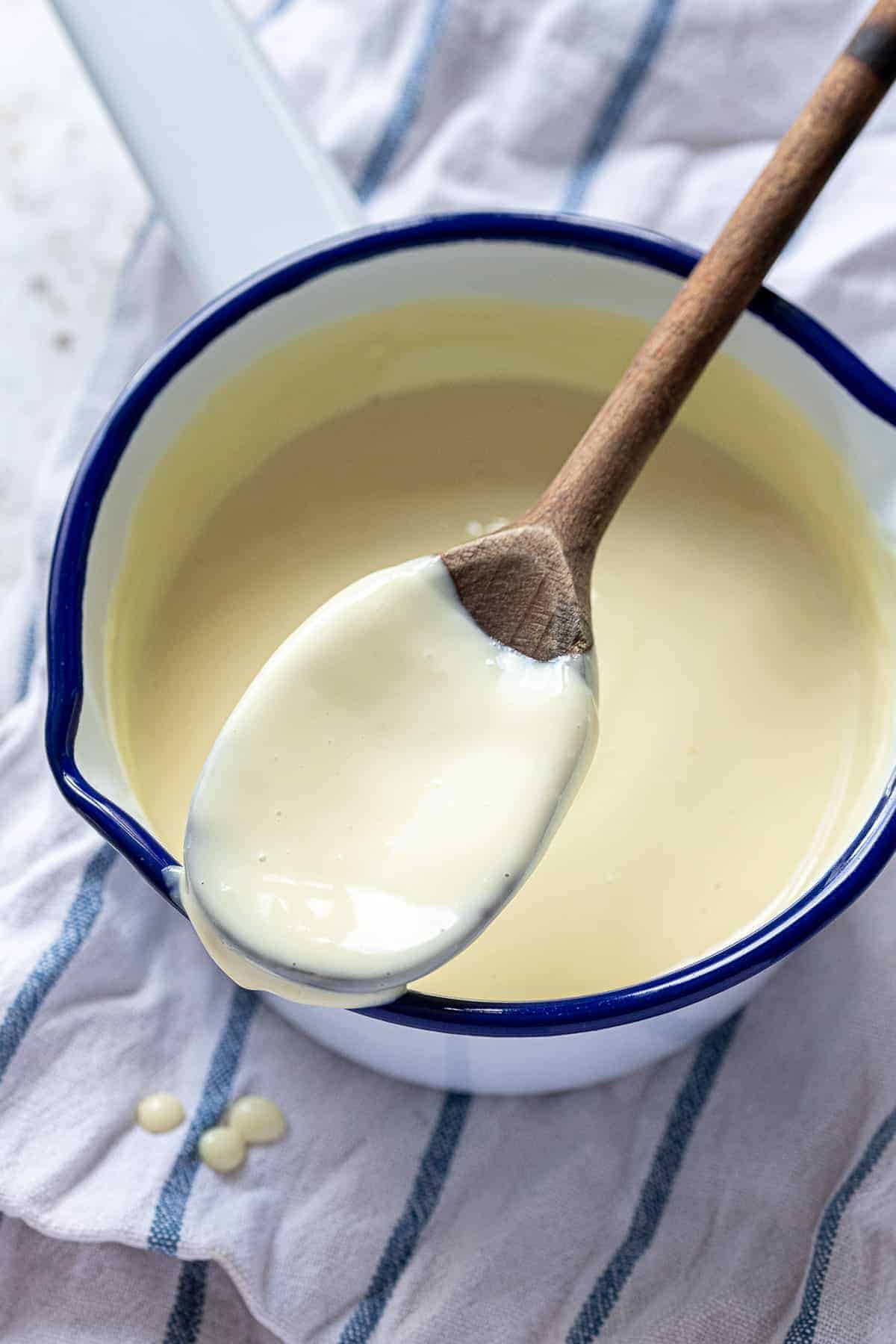 Close up of a wooden spoon covered in custard.