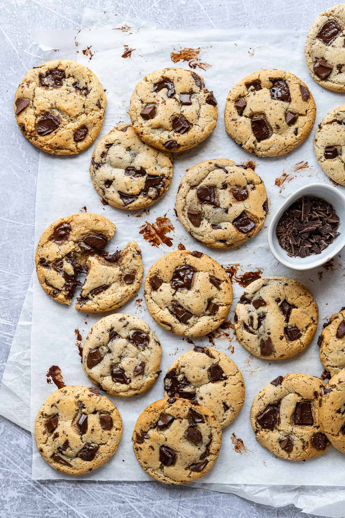 Vegan olive oil chocolate chip cookies and a bowl of chopped chocolate on a sheet of white baking parchment on a metal surface.