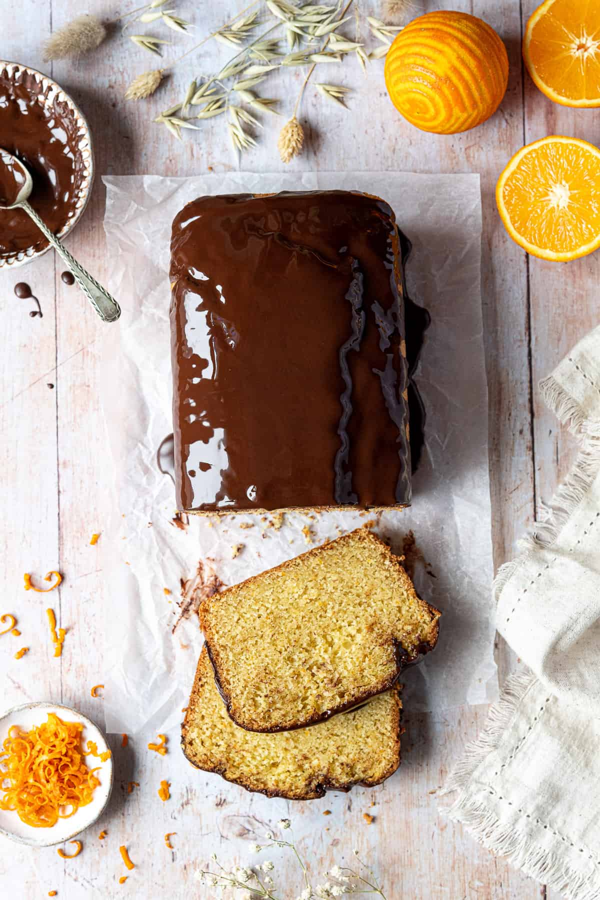 Vegan orange loaf cake on a wooden table with oranges, a bowl of chocolate glaze, a bowl of orange zest and a linen cloth.
