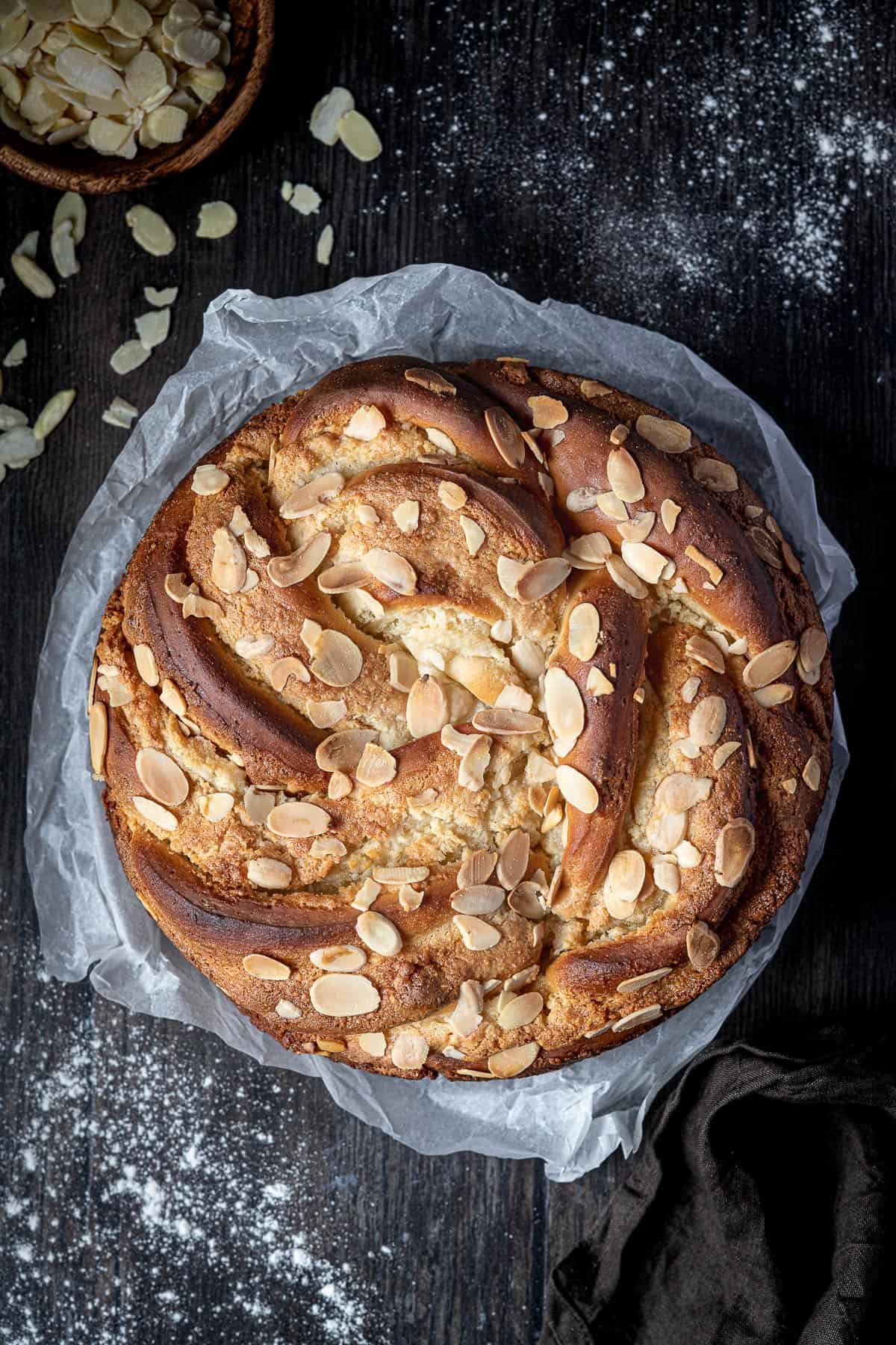 Almond bread twist on white baking parchment on a wooden table with a bowl of flaked almonds.