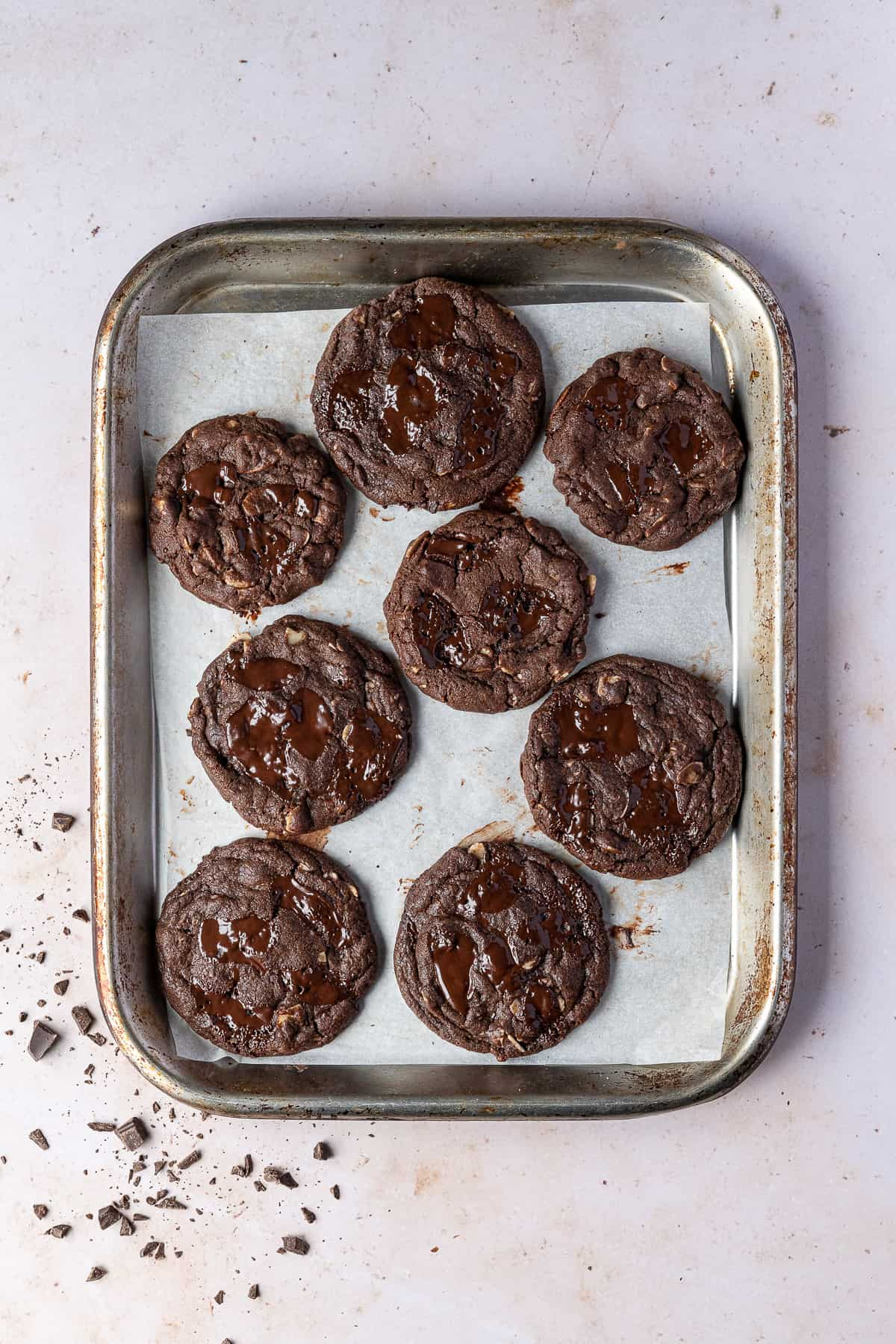 Vegan double chocolate almond cookies on a metal baking tray.