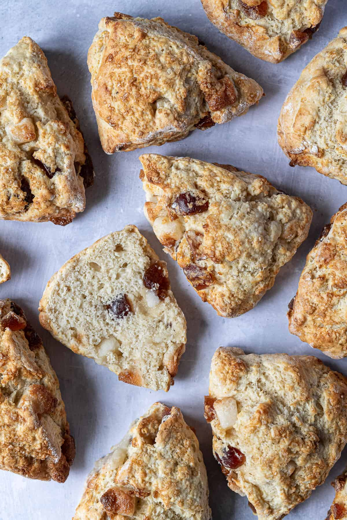 Vegan marzipan cherry scones on a grey surface, one sliced in half.