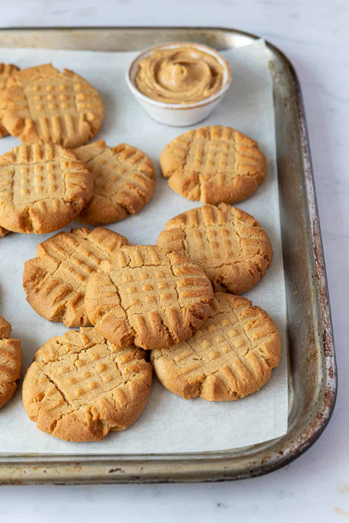 Peanut butter cookies on a metal baking tray.