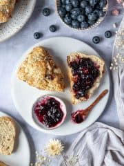 A scone sliced in half on a white plate with jam, surrounded by a bowl of blueberries, dried flowers, grey linen and plates of scones.