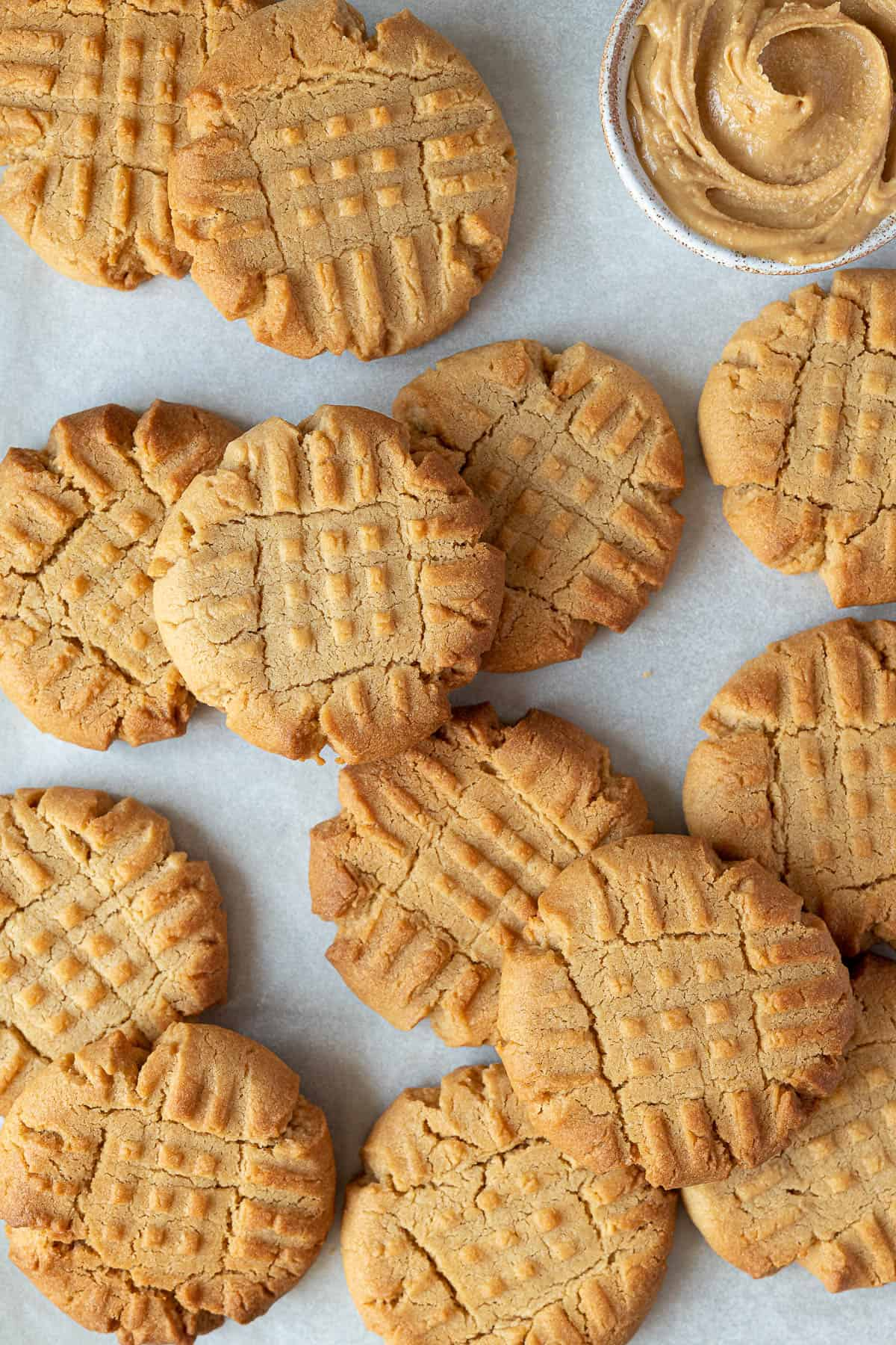 Close up of vegan peanut butter cookies with a bowl of peanut butter.